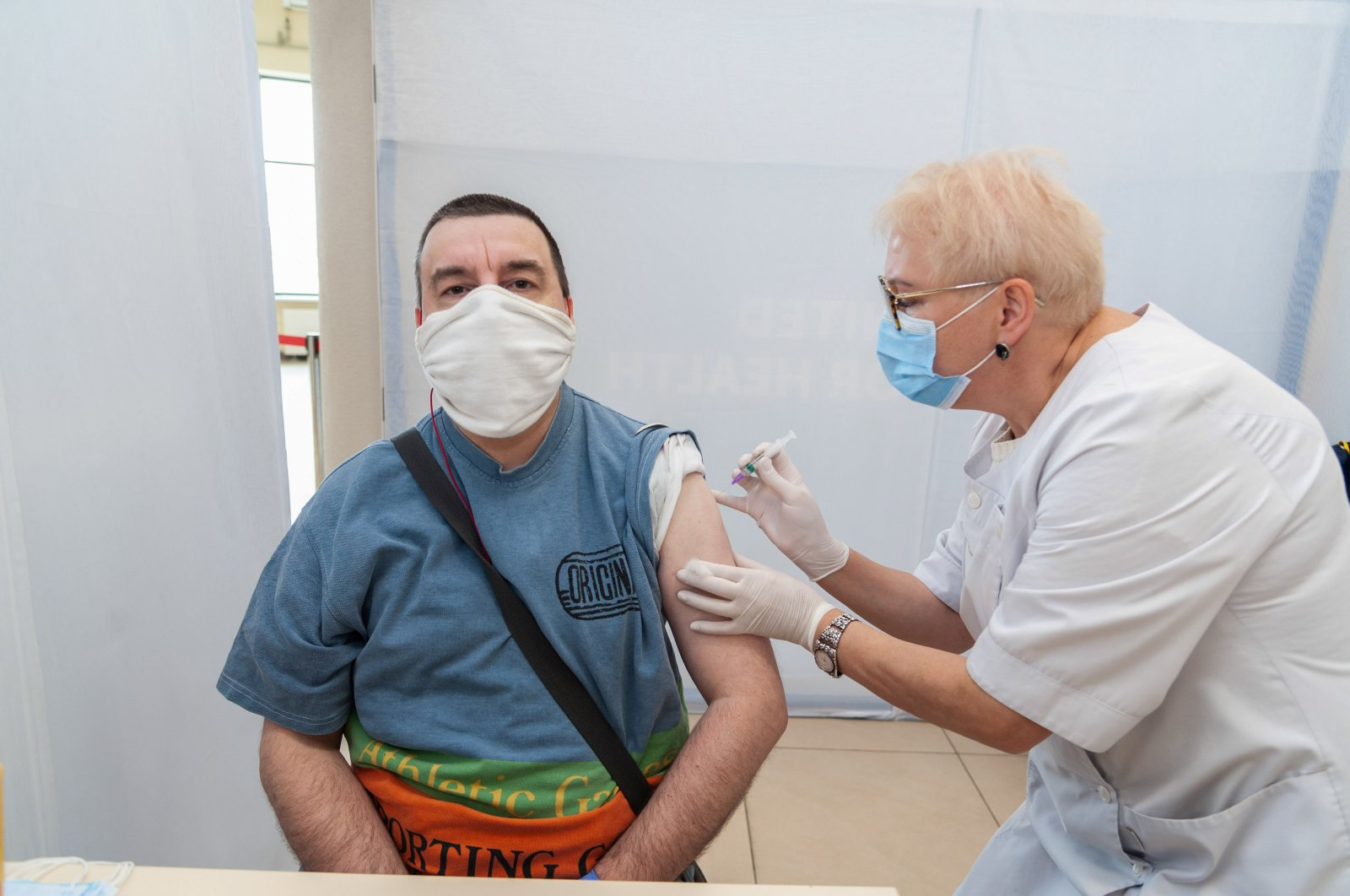 A healthcare worker administers a dose of Sinovac vaccine to a man at the Arena Lviv stadium, in Lviv, Ukraine, May 29, 2021. (Sipa USA via Reuters)