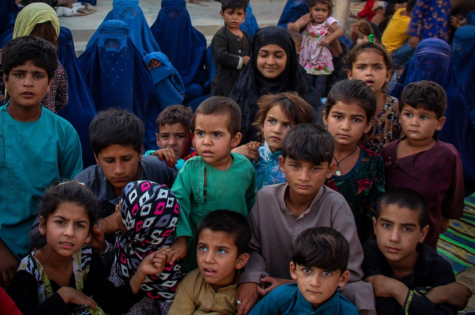 Children from internally displaced Afghan families arriving from the districts of Khan Abad, Ali Abad and Imam Sahib who fled from ongoing battles between Taliban and Afghan security forces, look on inside the premises of a school in Kunduz city, Afghanistan, June 26, 2021. (AFP Photo)