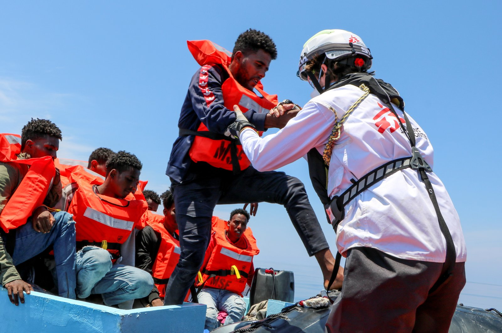 A member of the Doctors Without Borders (MSF) helps a migrant off a boat in the Mediterranean Sea, June 12, 2021. (Reuters Photo)