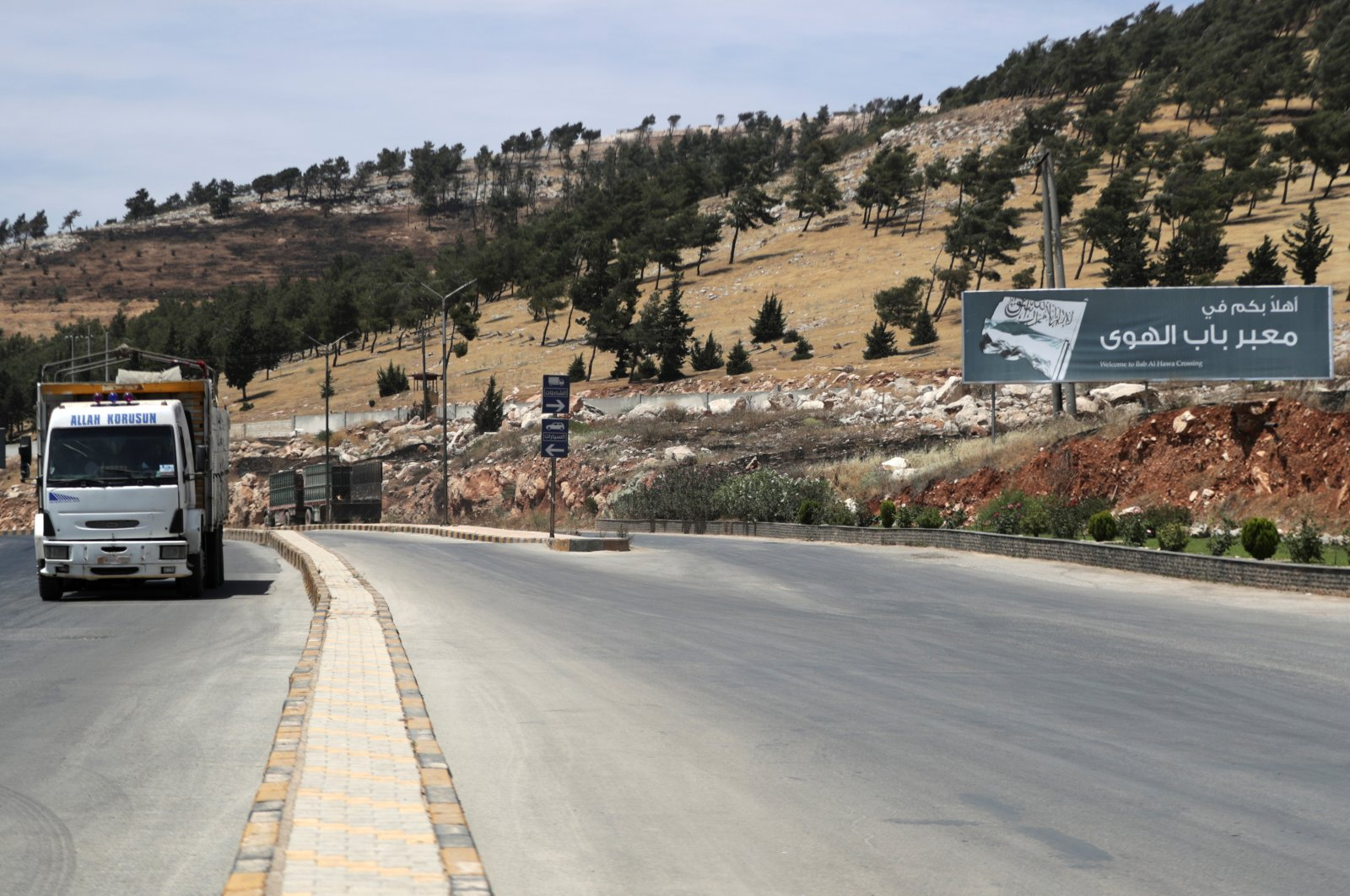"""A vehicle drives past a road sign that reads """"Welcome to Bab al-Hawa crossing,"""" Bab al-Hawa crossing at the Syrian-Turkish border, in Idlib governorate, Syria, June 10, 2021. (Reuters Photo)"""