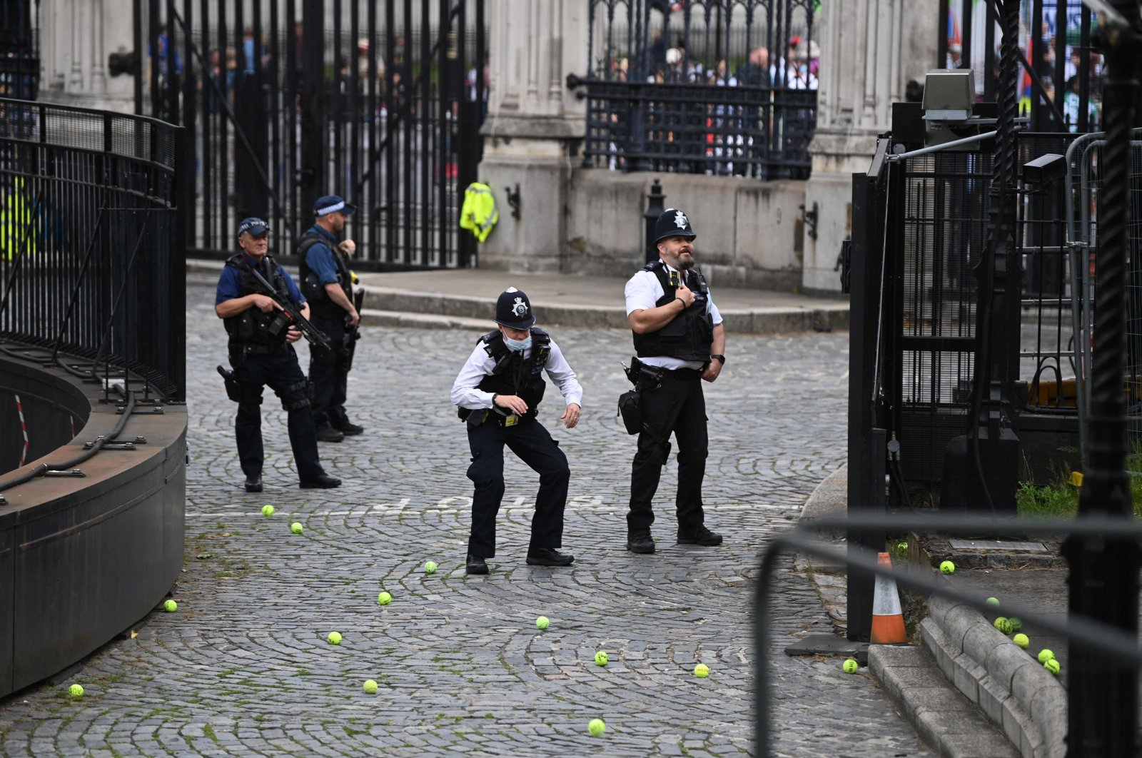 A policeman ducks as anti-vaccine and anti-lockdown protestors throw tennis balls at them in front of the U.K. Parliament, central London, June 26, 2021. (AFP Photo)