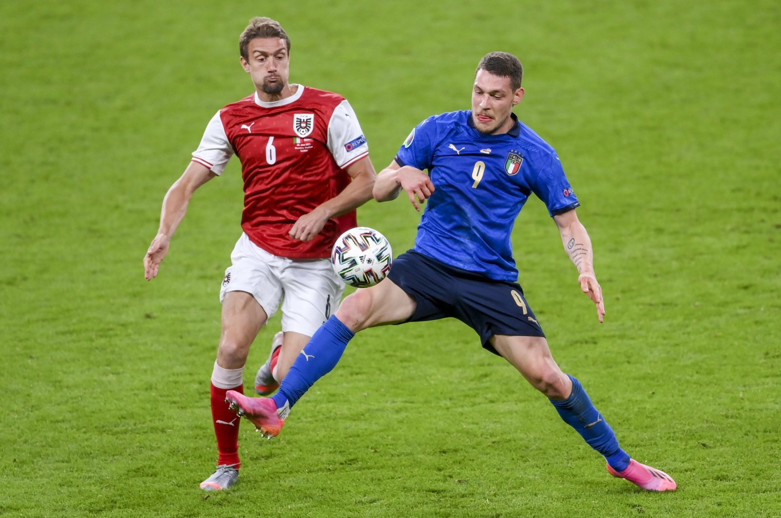 Austria's Stefan Ilsanker (L) and Italy's Andrea Belotti battle for the ball during the Euro 2020 round of 16 match between Italy and Austria at Wembley Stadium, London, U.K., June 26, 2021. (AP Photo)