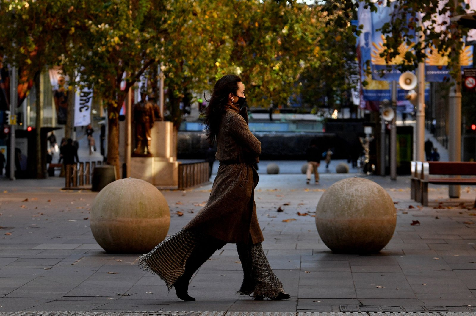 A woman wearing a face mask walks along a street in the central business district of Sydney as authorities locked down several central areas of Australia's largest city to contain an outbreak of the highly contagious delta variant, Sydney, Australia, June 25, 2021.  (AFP Photo)