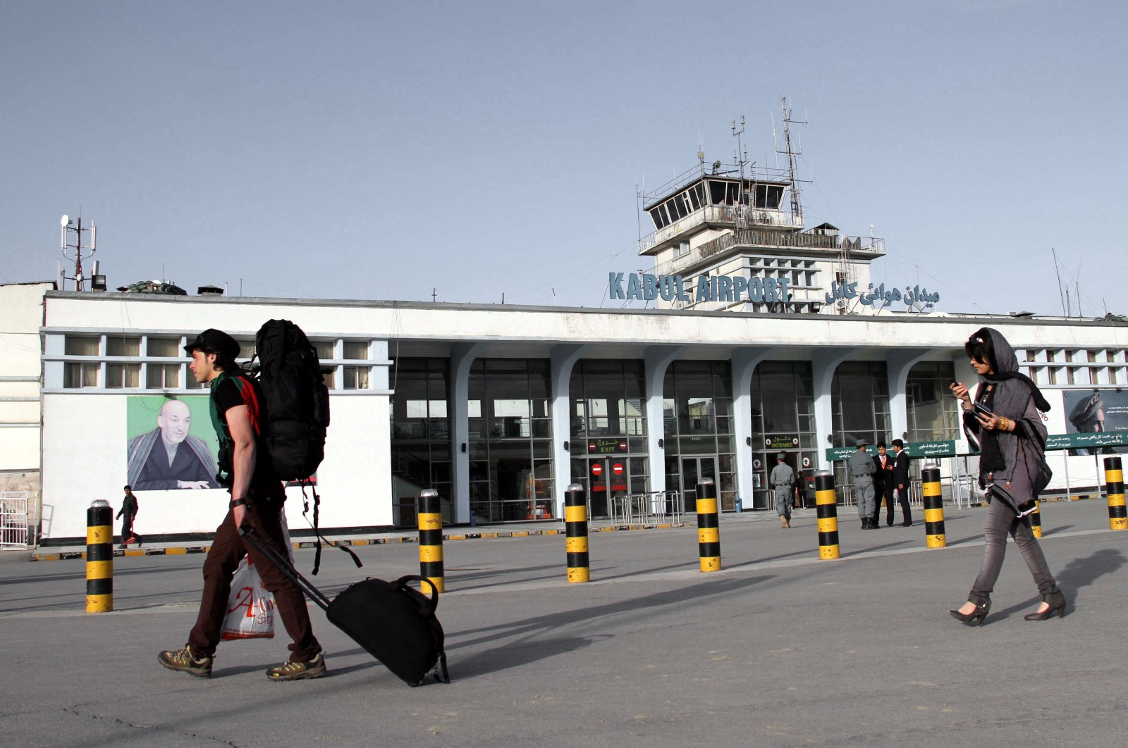 Passengers pass a portrait of Afghan President Hamid Karzai at Kabul International Airport, in Kabul, Afghanistan, March 26, 2012. (EPA Photo)