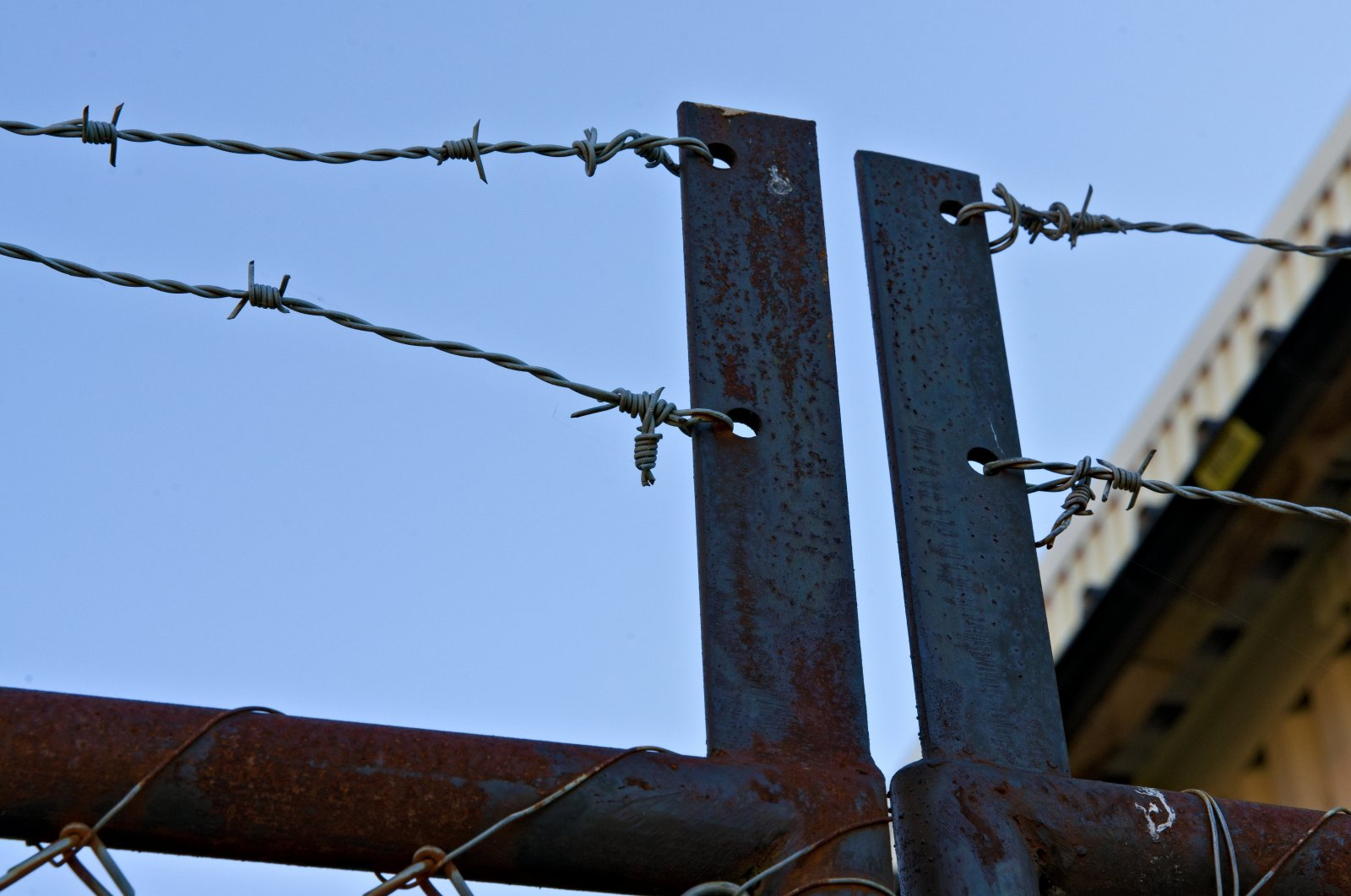 Rusted gate topped with barbed wire (Shutterstock)