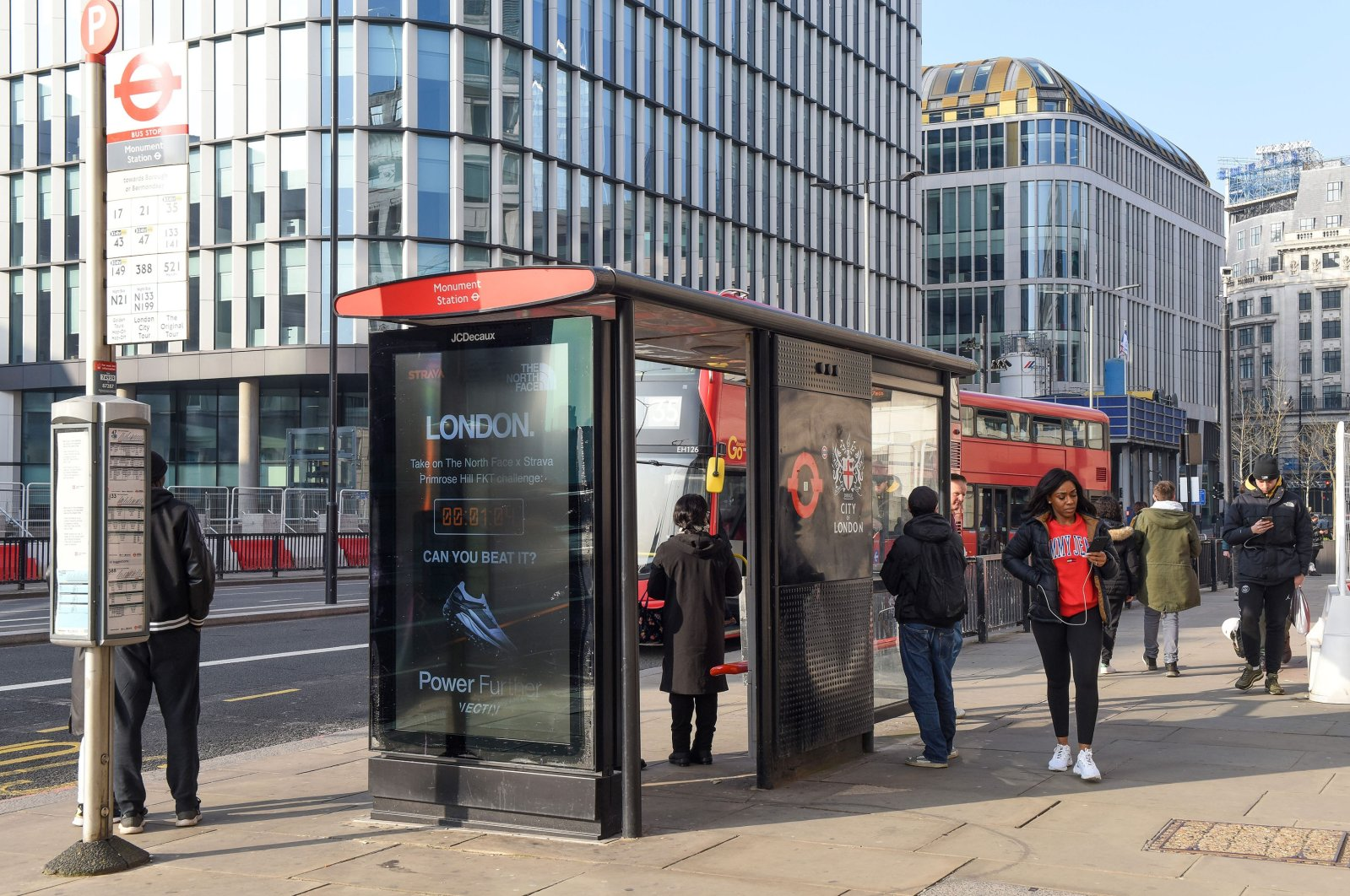 Commuters waiting for the bus at a bus stop in London, U.K., March 2, 2021. (Reuters Photo)