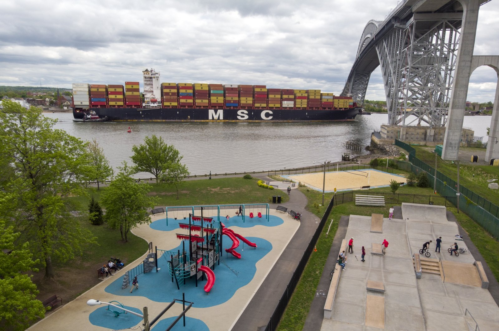 A container ship passes near a playground and a skate park at Bayonne Bridge in Bayonne, New Jersey, U.S., May 10, 2021. (AP Photo)