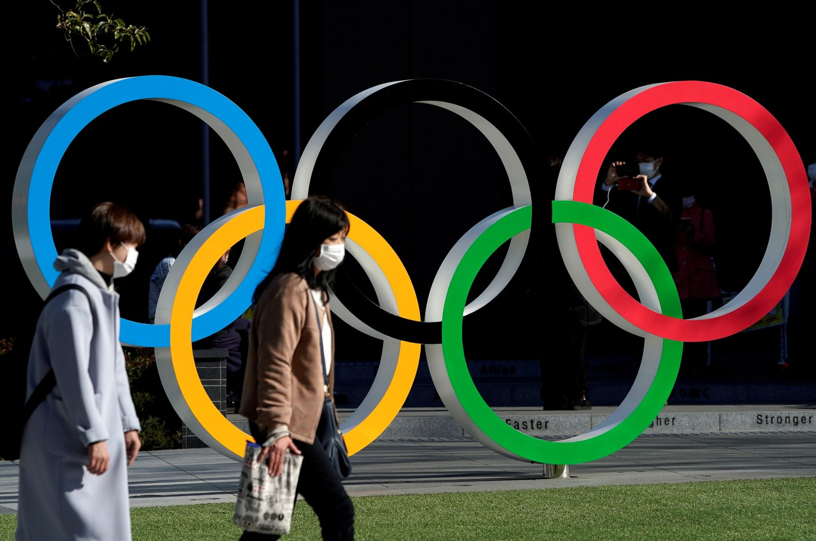 Women wearing protective face masks against COVID-19 walk past the Olympic rings in front of the Japan Olympics Museum, Tokyo, Japan, March 25, 2020. (Reuters Photo)