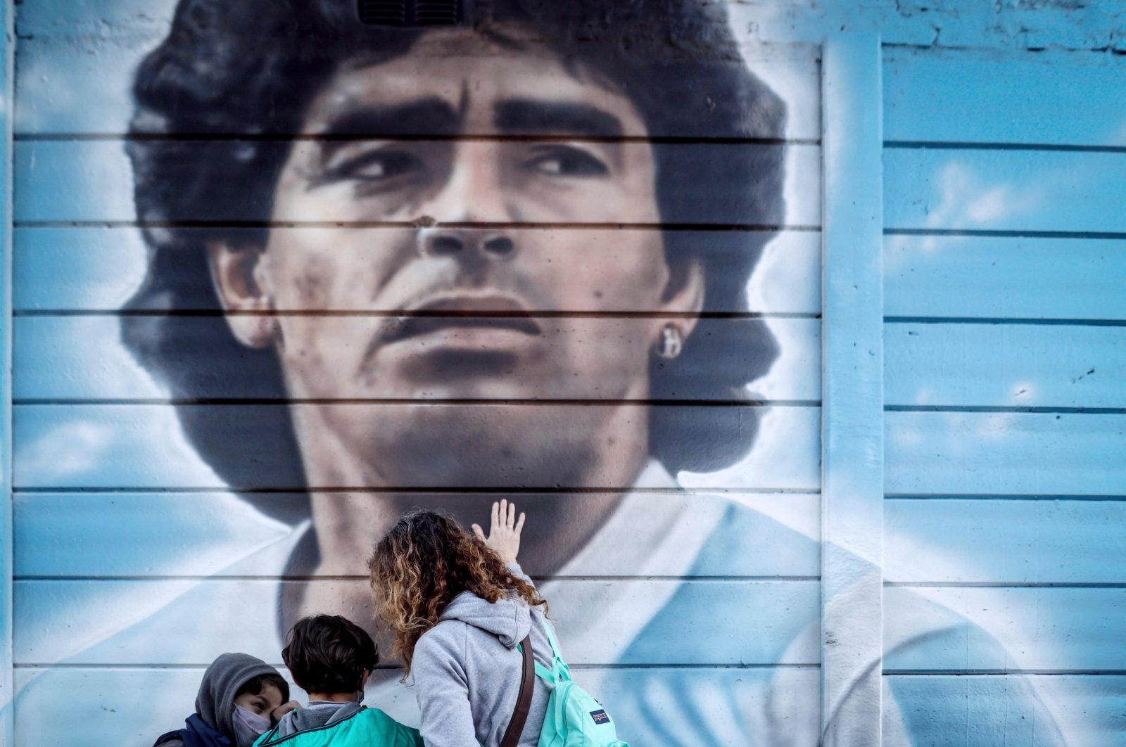 A woman and her children look at a mural of Diego Armando Maradona, as they commemorate 35 years of the goal that the Argentine star scored against England in the Mexico 1986 World Cup, in Buenos Aires, Argentina, June 22, 2021. (EPA Photo)