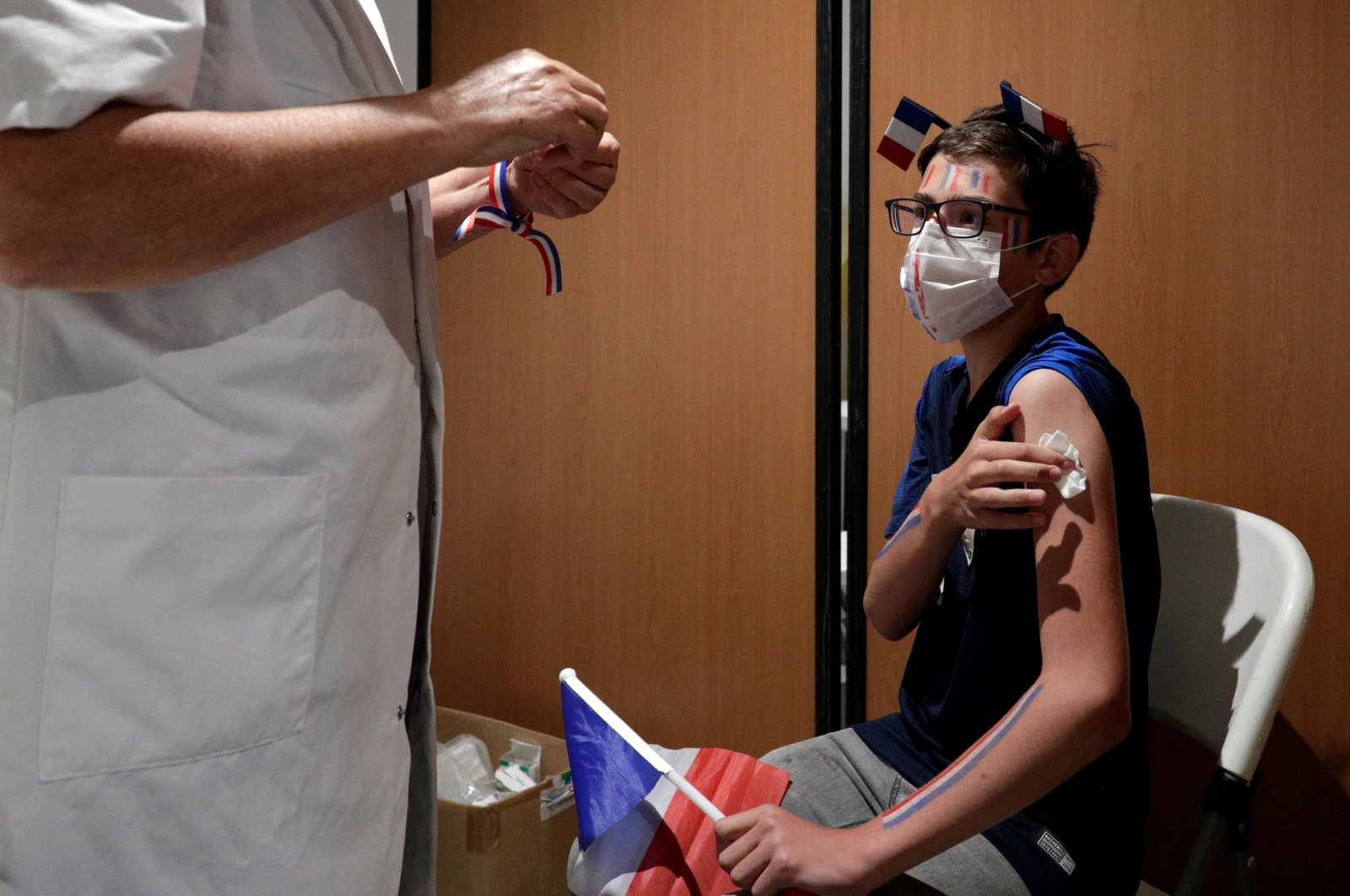 A French supporter receives a dose of the Pfizer COVID-19 vaccine during a vaccination drive at the Armand Peugeot Fan-zone, where fans watch the broadcast of the UEFA Euro 2020 Group F football match between France and Portugal in Poissy, outside Paris, France, on June 23, 2021. (AFP Photo)