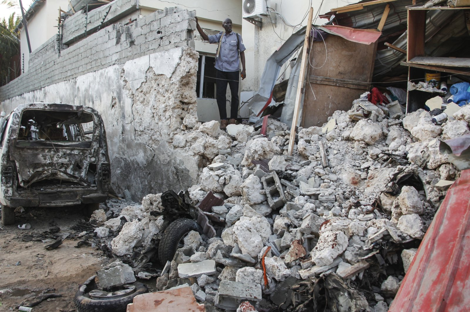 A hotel security guard stands by wreckage in the aftermath of an attack on the Afrik hotel in Mogadishu, Somalia, Feb. 1, 2021. (AP File Photo)