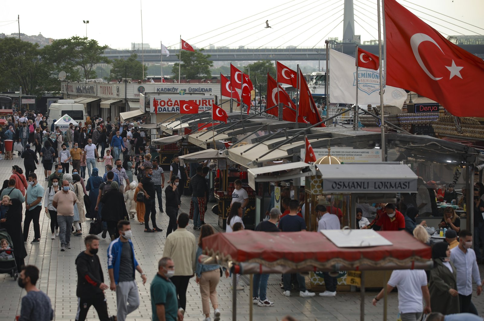 People walk in Eminönü hours before the start of a weekend curfew in Istanbul, Friday, May 28, 2021. (AP File Photo)