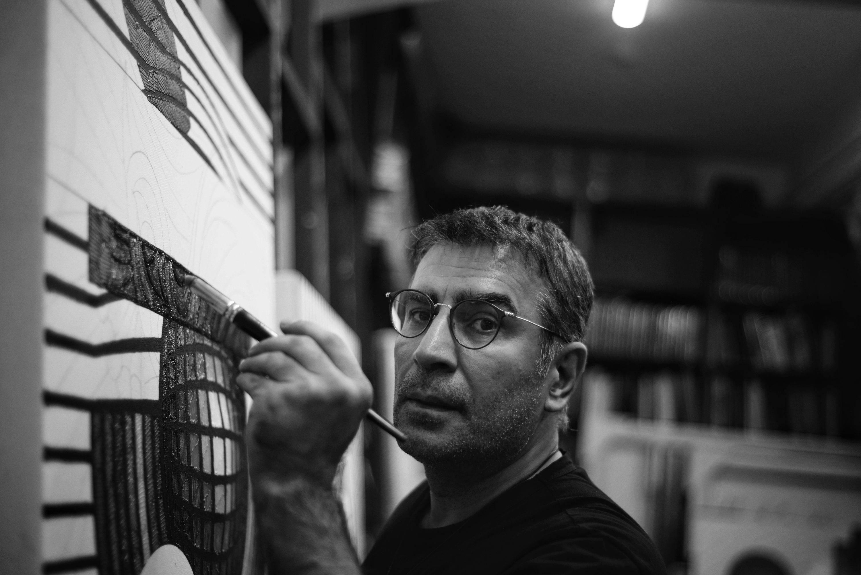 Ahmet Güneştekin poses while painting.