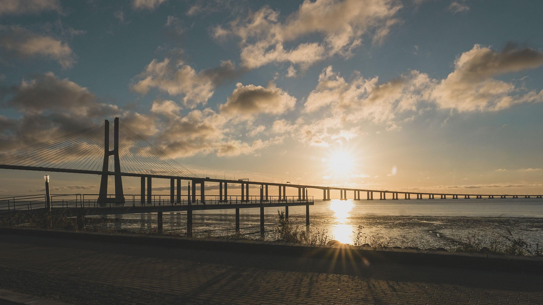 O sol nasce sobre a Ponte Vasco da Gama, em Lisboa, Portugal.  (Foto do Shutterstock)