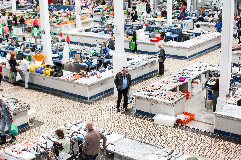 As pessoas compram peixes no novo mercado de peixes Mercado du Livremento em Setupal, Portugal.  (Foto do Shutterstock)