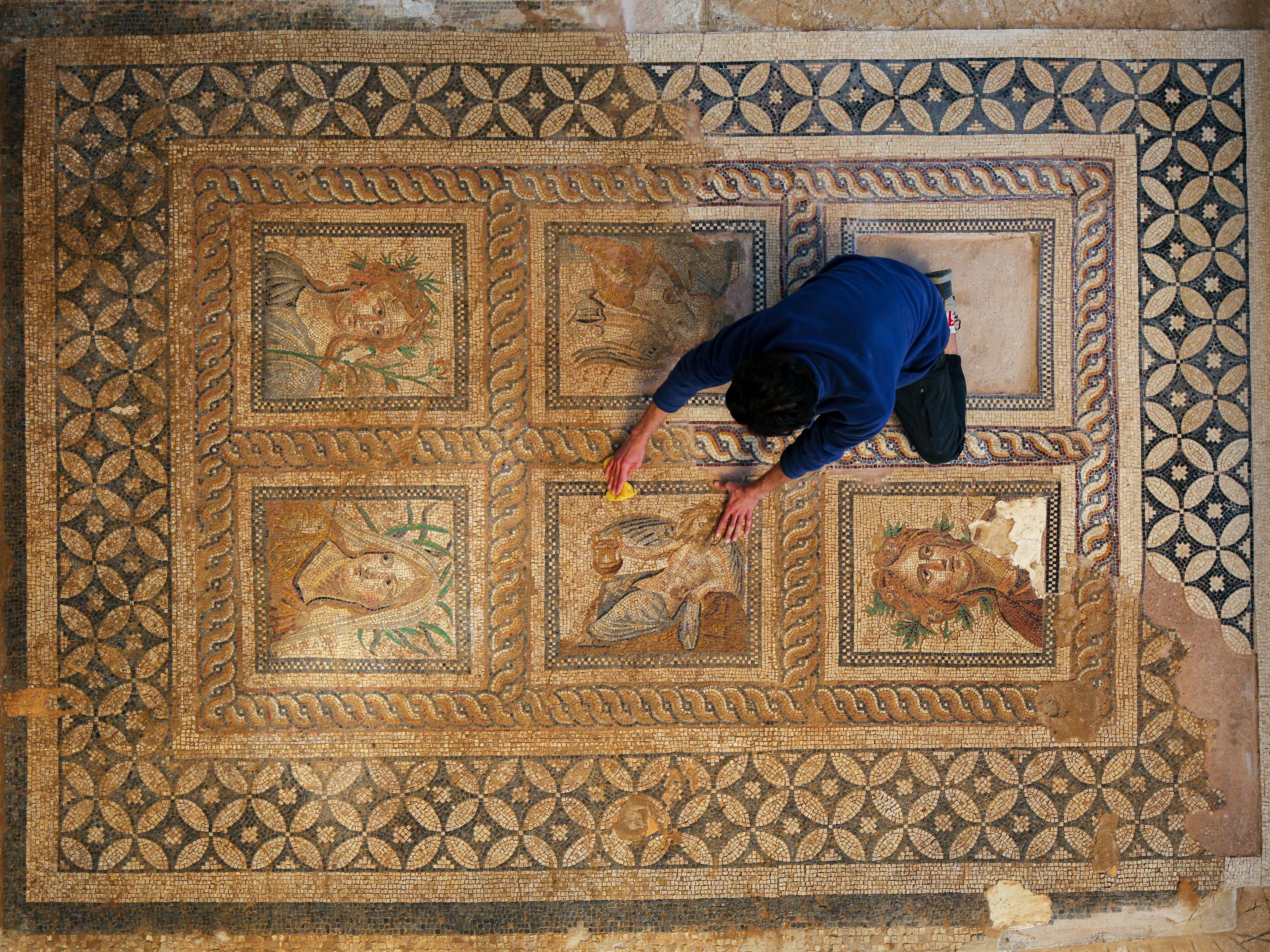 An official cleans the mosaics found in the ancient city of Metropolis, Izmir, western Turkey, June 28, 2021. (AA Photo)