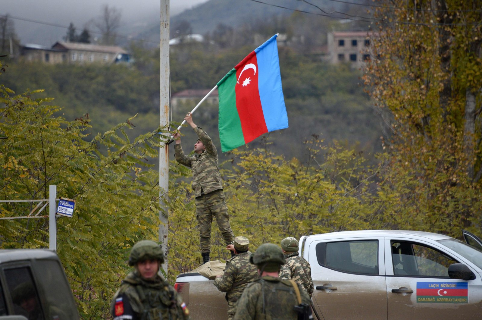 An Azerbaijani soldier fixes the national flag on a lamp post in the town of Lachin, Azerbaijan, on Dec. 1, 2020. (AFP Photo)
