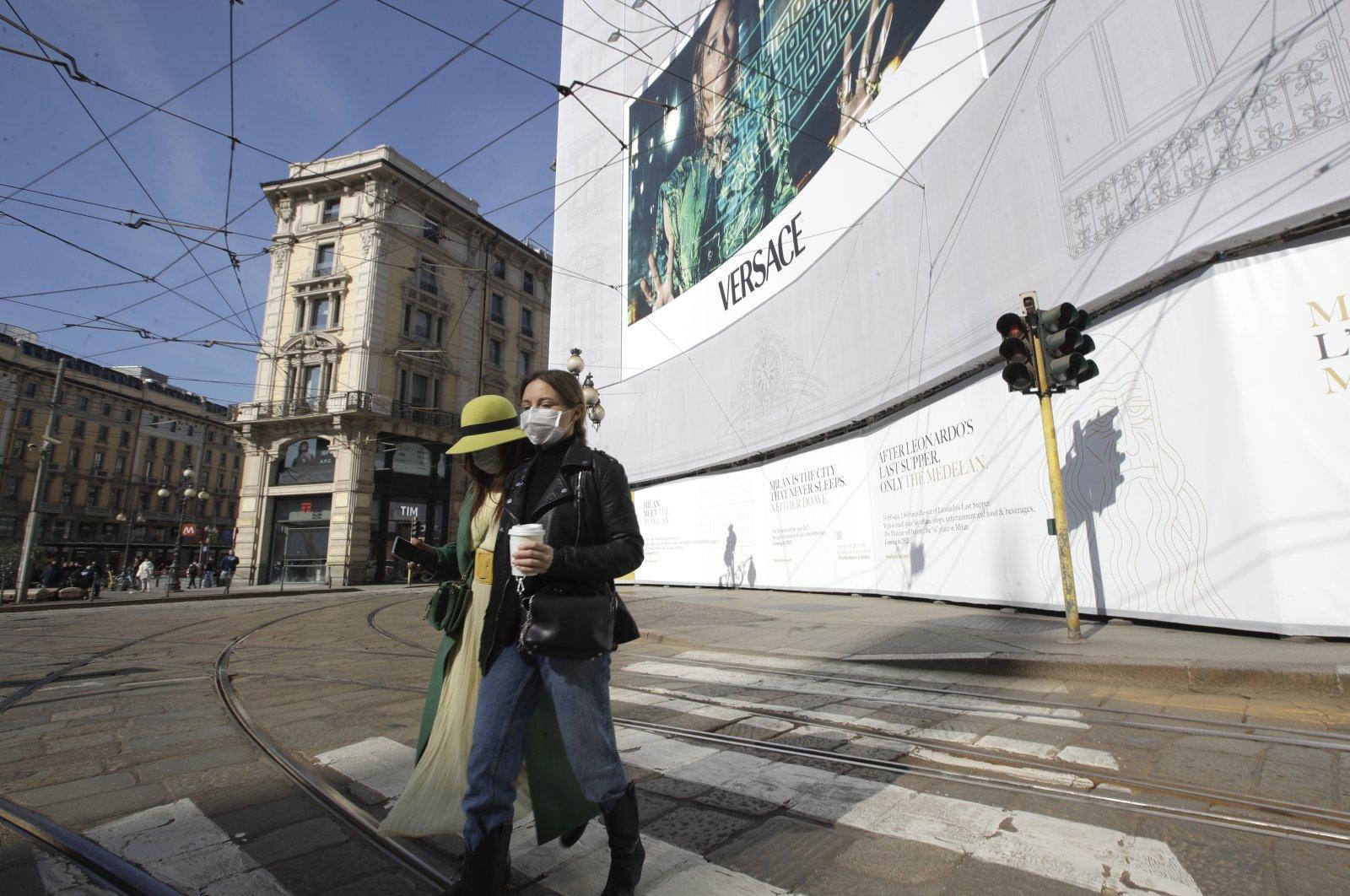 Women wearing sanitary masks walk in downtown Milan, Italy, Feb. 24, 2020. (AP Photo)