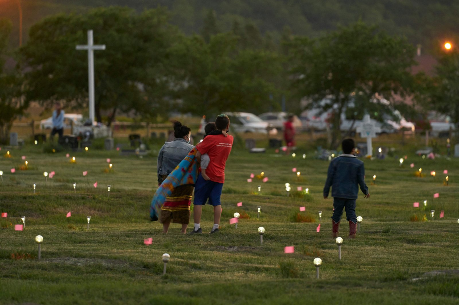 A family walks through a field where flags and solar lights now mark the site where human remains were discovered in unmarked graves at the former Marieval Indian Residential School site on Cowessess First Nation, Saskatchewan, Canada, June 26, 2021. (AFP Photo)