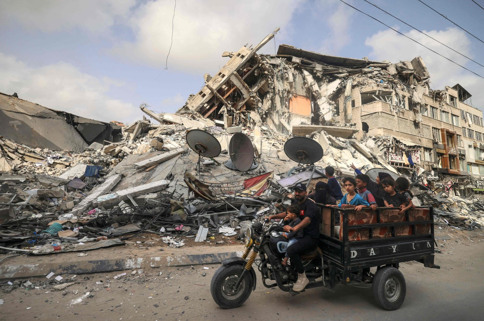 A Palestinian man transports children in a tricycle past the Al-Shuruq building, destroyed by an Israeli airstrike, after a cease-fire was agreed upon between Israel and Hamas, in Gaza City, Palestine, May 21, 2021. (AFP Photo)