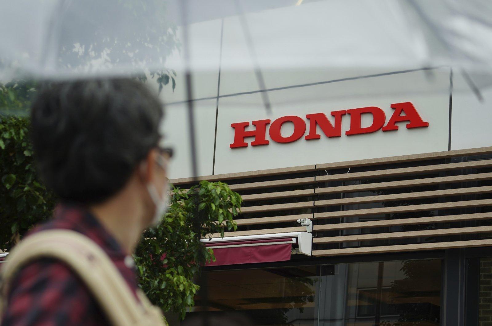 A man wearing a protective mask walks past the logo of Honda Motor Company, in Tokyo, Japan, May 13, 2021. (AP Photo)