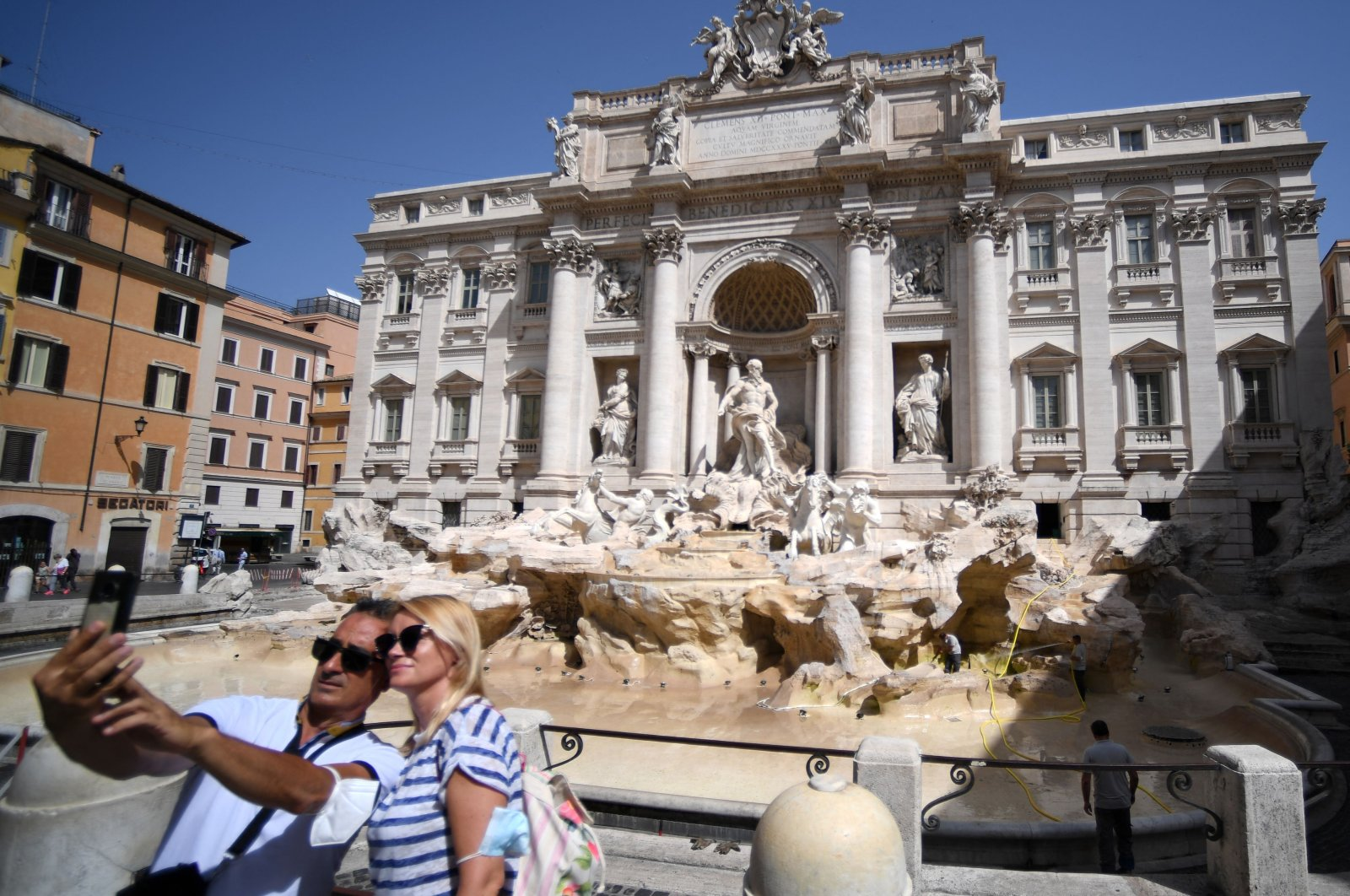 A couple poses for a selfie without protective face masks in front of the Trevi Fountain in Rome, Italy, June 28, 2021. (AFP Photo)