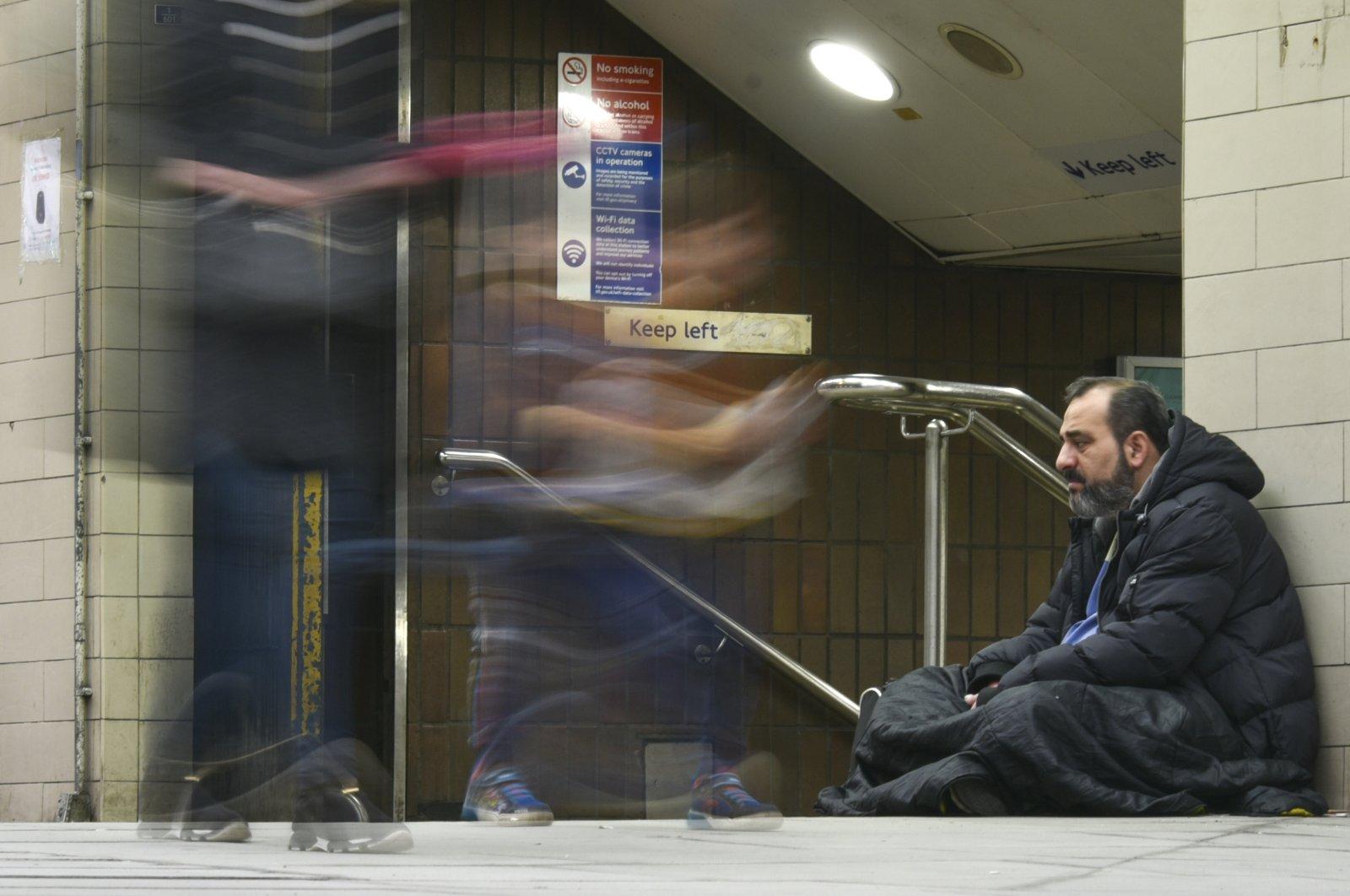 People walk past a homeless man outside Bond Street underground station, London, the U.K., Dec. 22, 2020. (AP Photo)