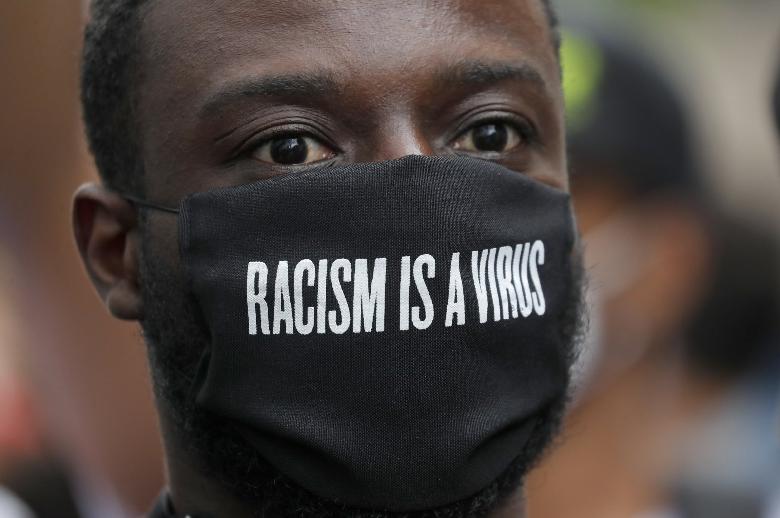 A protester wears a face mask in front of the U.S. embassy, during the Black Lives Matter protest rally in London, June 7, 2020. (AP Photo)