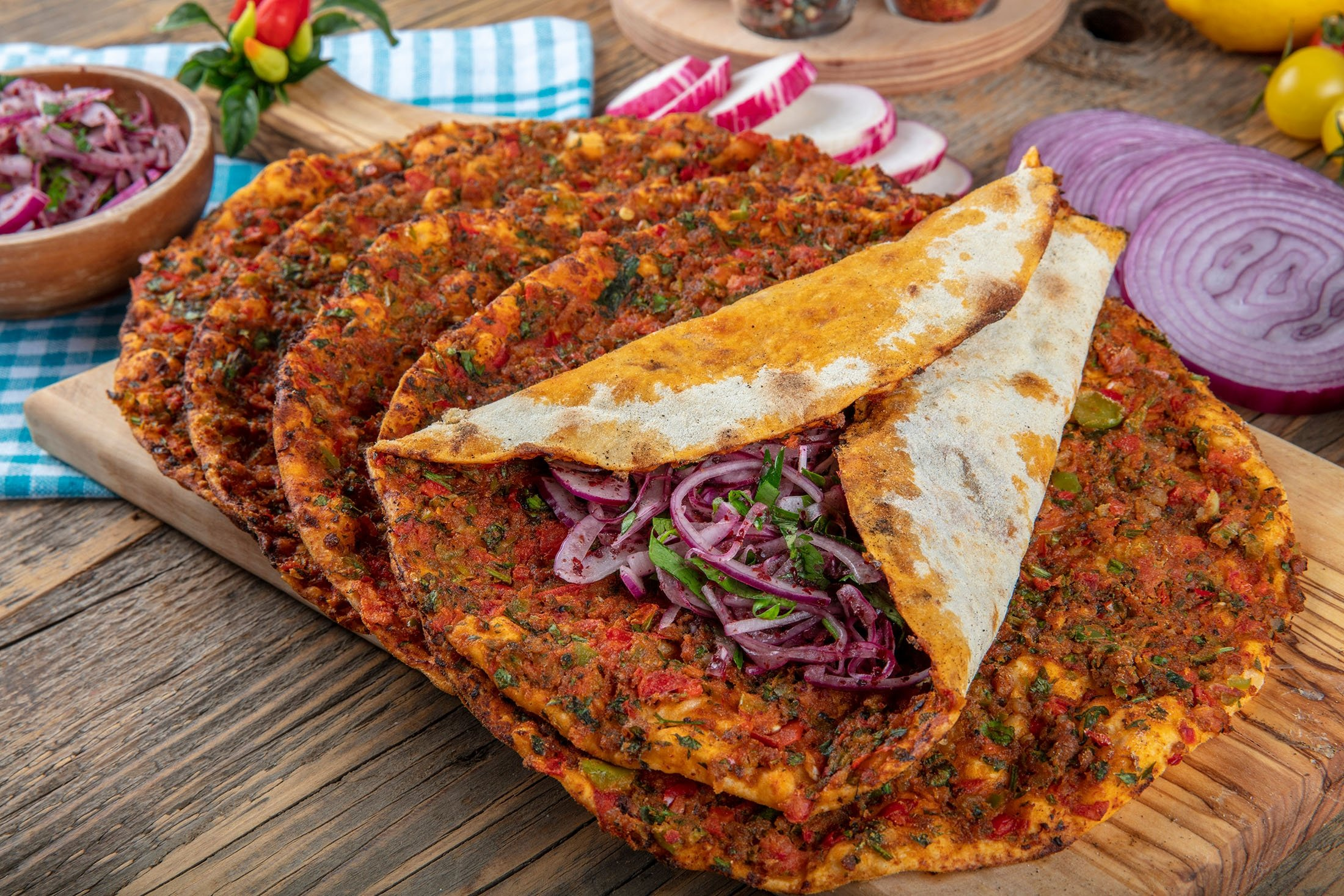 Lahmacun is a round, thin piece of dough topped with minced meat, minced vegetables and herbs. (Shutterstock Photo)