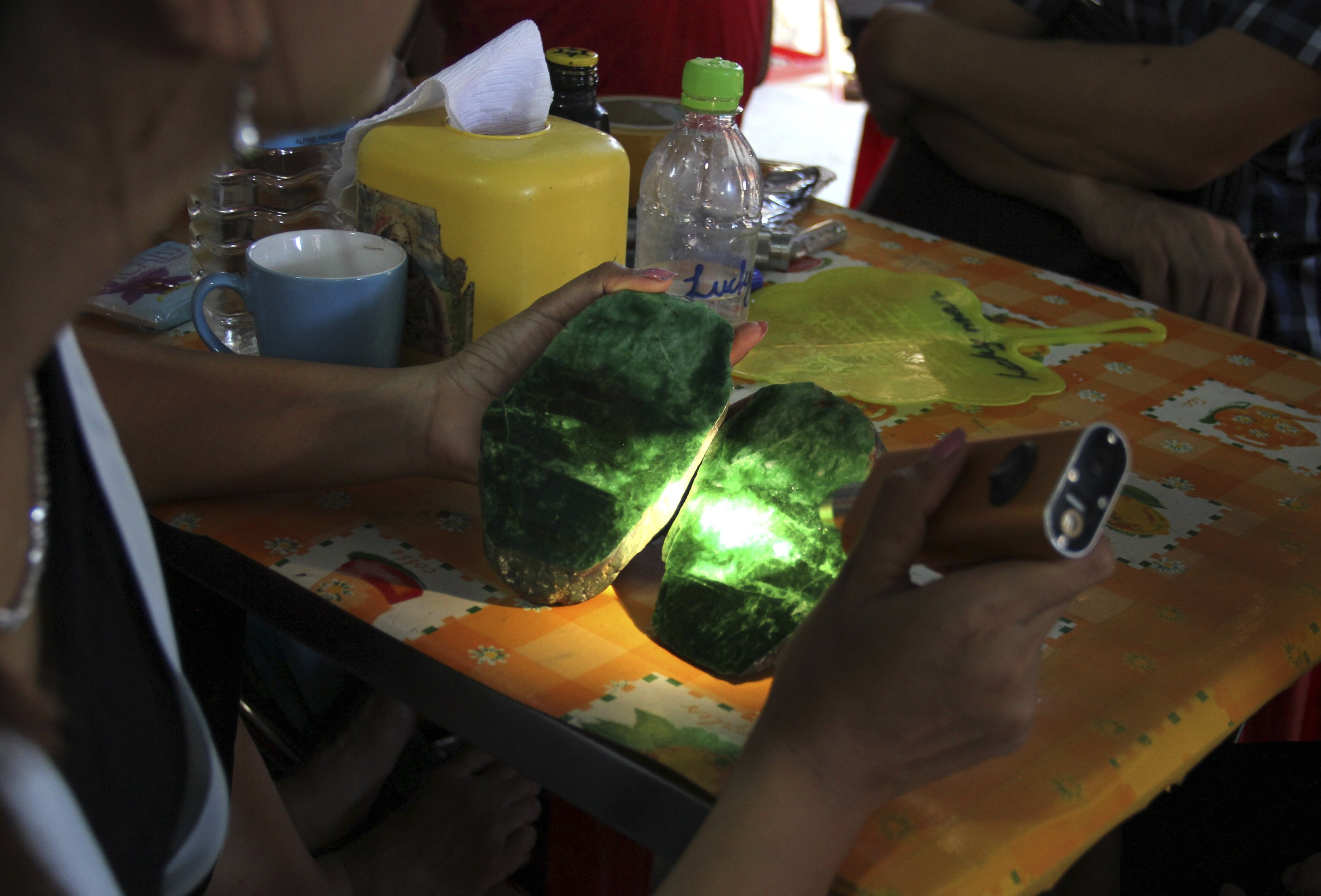 Local people examine the quality of a jade stone in the Hpakant area of Kachin state, northern Myanmar, Sept. 18, 2015. (AP Photo)