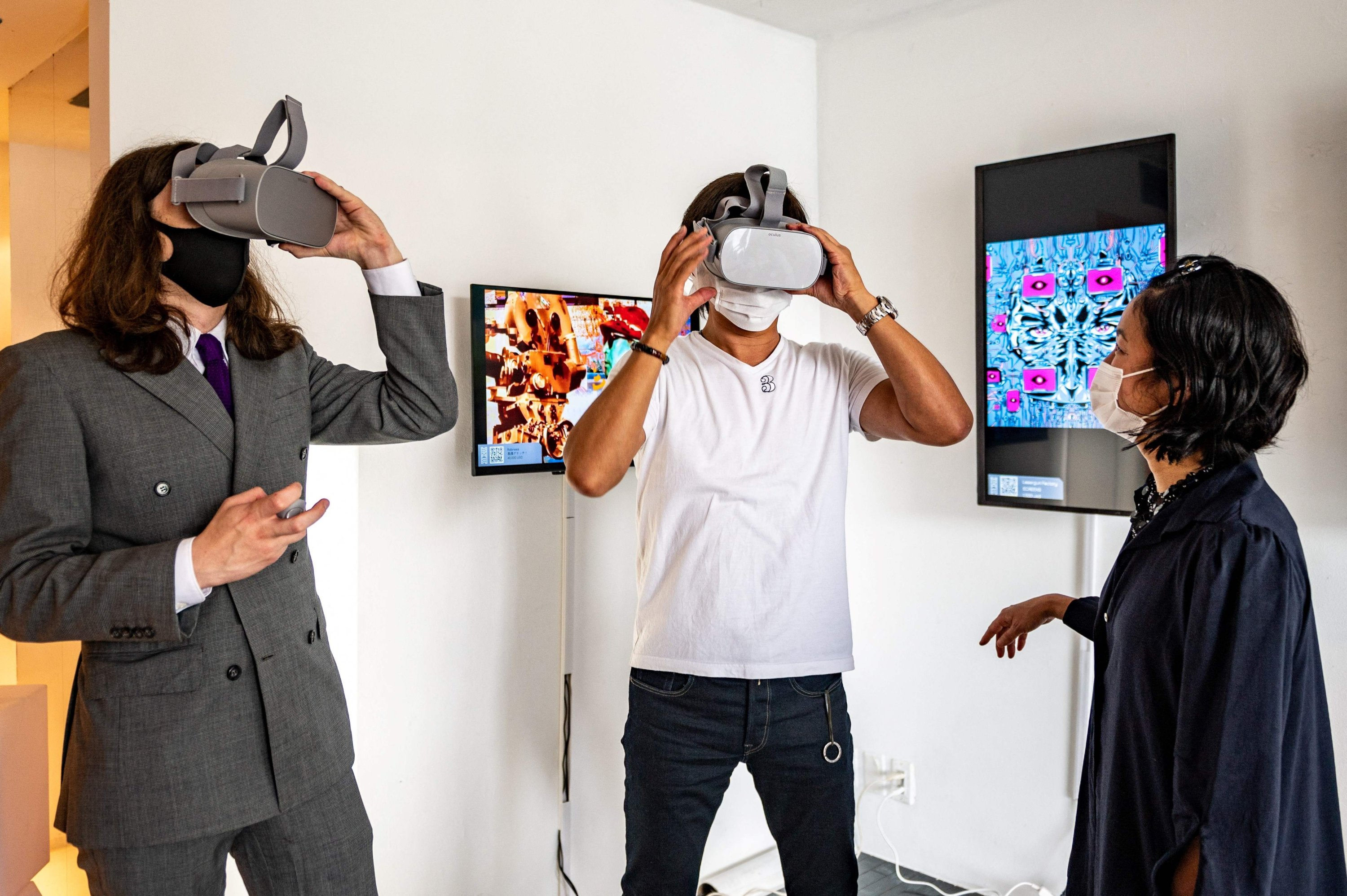 CEO of the BAE, a crypto art platform, and the exhibition's curator, Sascha Bailey (L), demonstratesa virtual reality (VR) device to a visitor (C) during 'CrypTOKYO', a physical blockchain art exhibition in Tokyo, Japan, June 25, 2021. (Philip Fong via AFP)