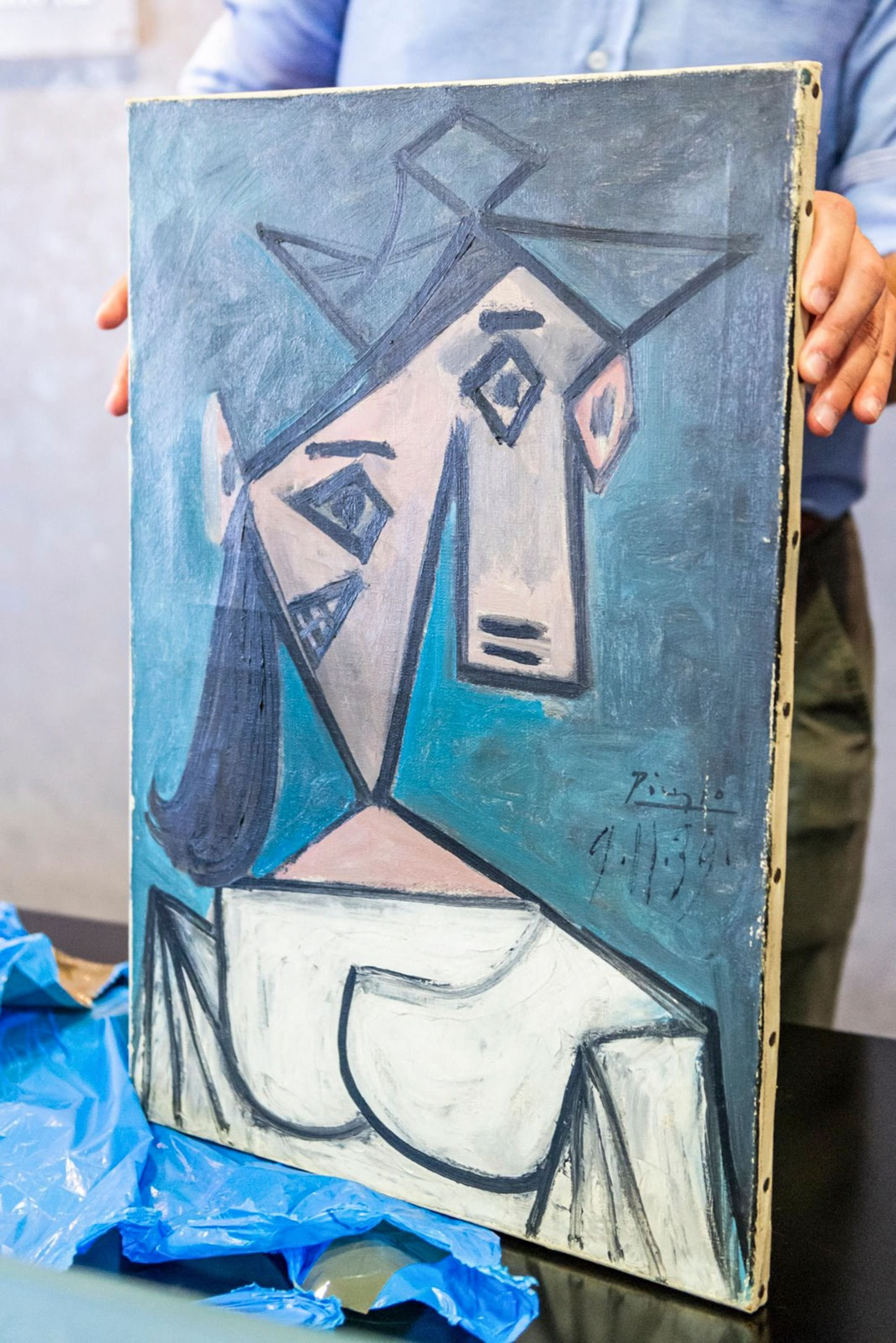 An official presents a recovered painting of Pablo Picasso titled 'Head of a Woman', in Athens, Greece,June 29, 2021. (Greek Police via AFP)