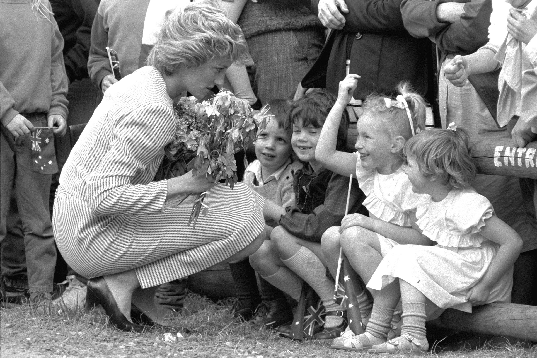 Britain's Princess Diana stoops to speak to children during a visit to Macedon, Australia, Feb. 11, 1985. (AP Photo)
