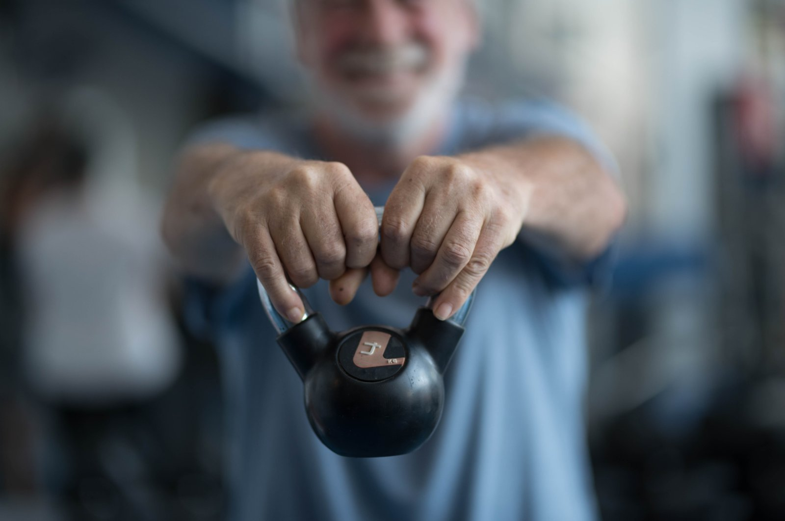 An elderly man holding a weight at the gym. (Shutterstock Photo)