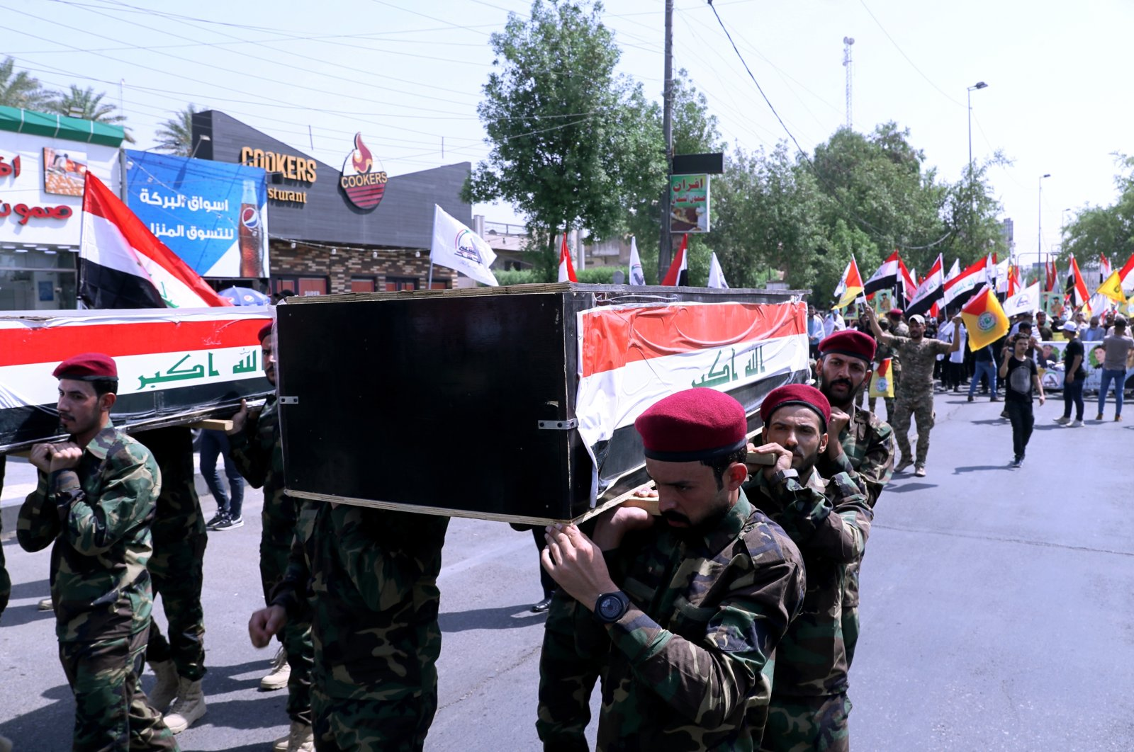 Popular Mobilization Forces fighters carry flag-draped coffins of slain fighters who were killed during airstrikes during their symbolic funeral in Baghdad, Iraq, Tuesday, June 29, 2021. (AP Photo)