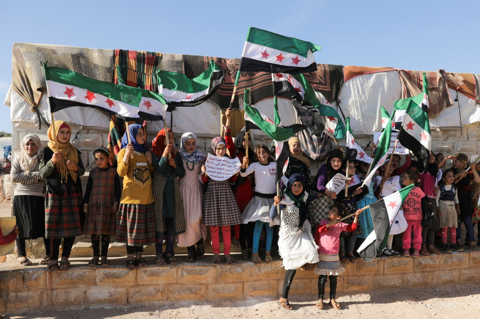 Internally displaced Syrian girls hold Syrian opposition flags during a protest against the closure of Bab al-Hawa crossing in the opposition-held Idlib, northwestern Syria, June 7, 2021. (REUTERS Photo)