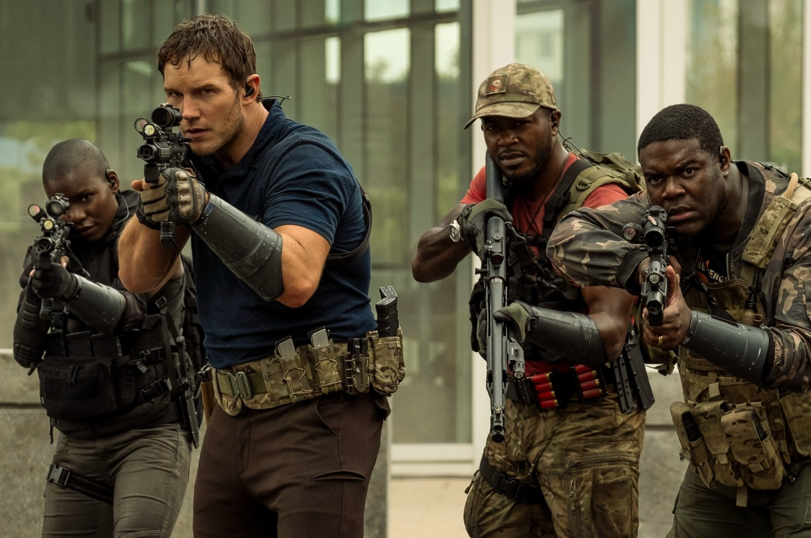 """Chris Pratt (C-L), Edwin Hodge (C-R) and Sam Richardson (R) walk together holding weapons, in a scene from """"The Tomorrow War."""" (Amazon via AP)"""