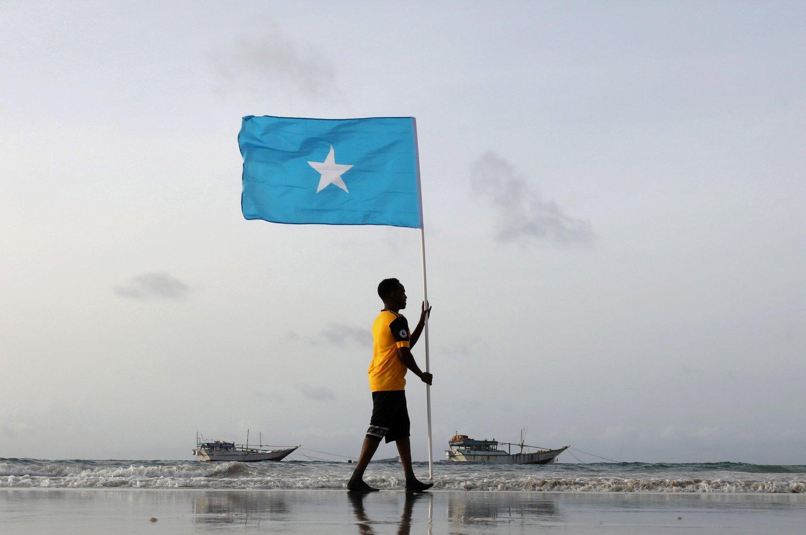 A Somali youth holds the national flag, at Lido beach, Mogadishu's Abdiaziz District, Somalia June 18, 2021. (Reuters Photo)