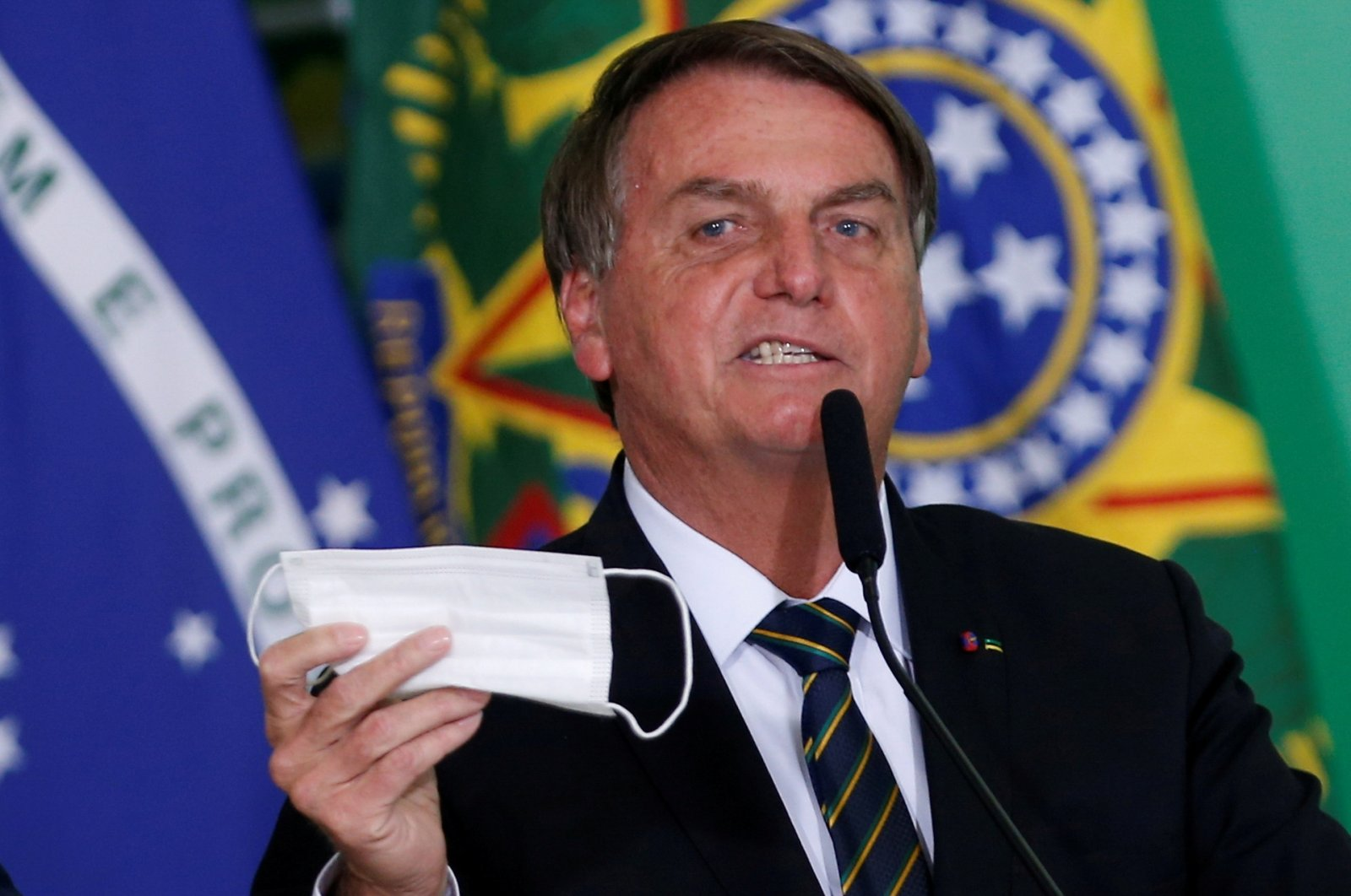 Brazil's President Jair Bolsonaro holds his protective face mask during a ceremony at the Planalto Palace, amid the coronavirus pandemic, in Brasilia, Brazil, June 10, 2021. (Reuters Photo)