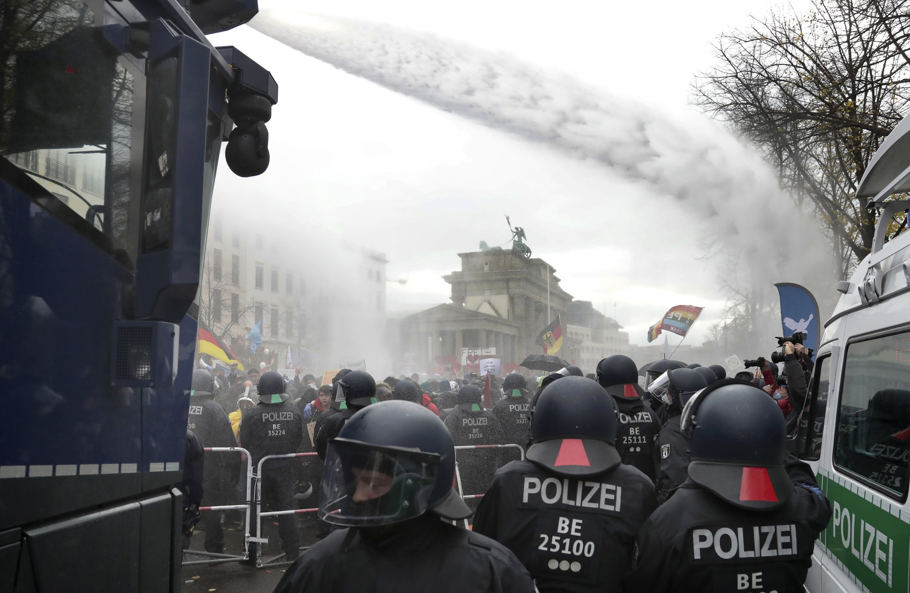 Police use water cannons to clear a blocked road between the Brandenburg Gate and the Reichstag building, home of the German federal parliament, as people attend a protest rally against the coronavirus restrictions in Berlin, Germany, Nov. 18, 2020. (AP Photo)