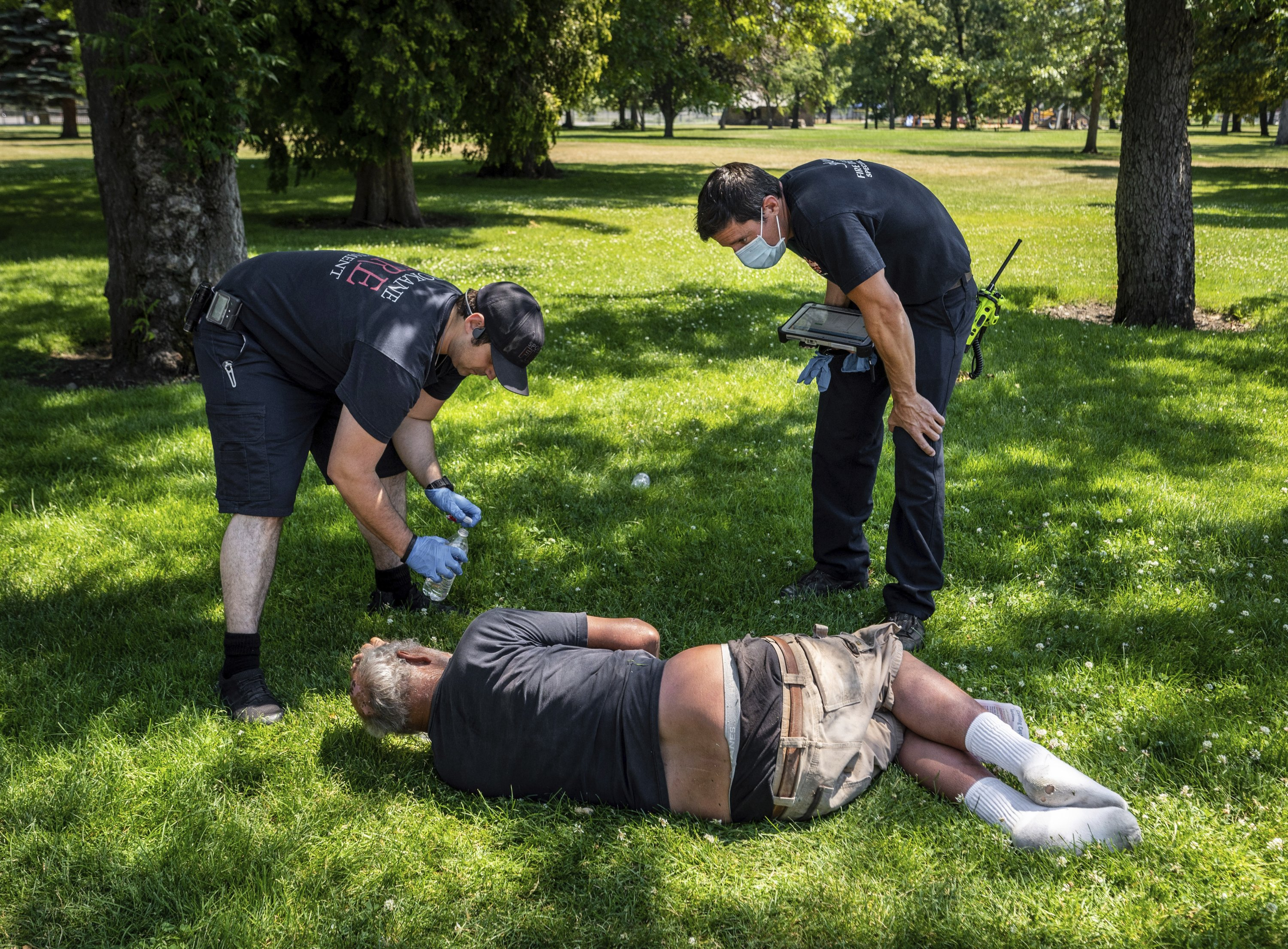 With the temperature well over 100 degrees, Spokane, Wash., firefighter Sean Condon, left and Lt. Gabe Mills, assigned to the Alternative Response Unit of of Station 1, check on the welfare of a man in Mission Park in Spokane, Washington, D.C., U.S., June 29, 2021. (AP Photo)