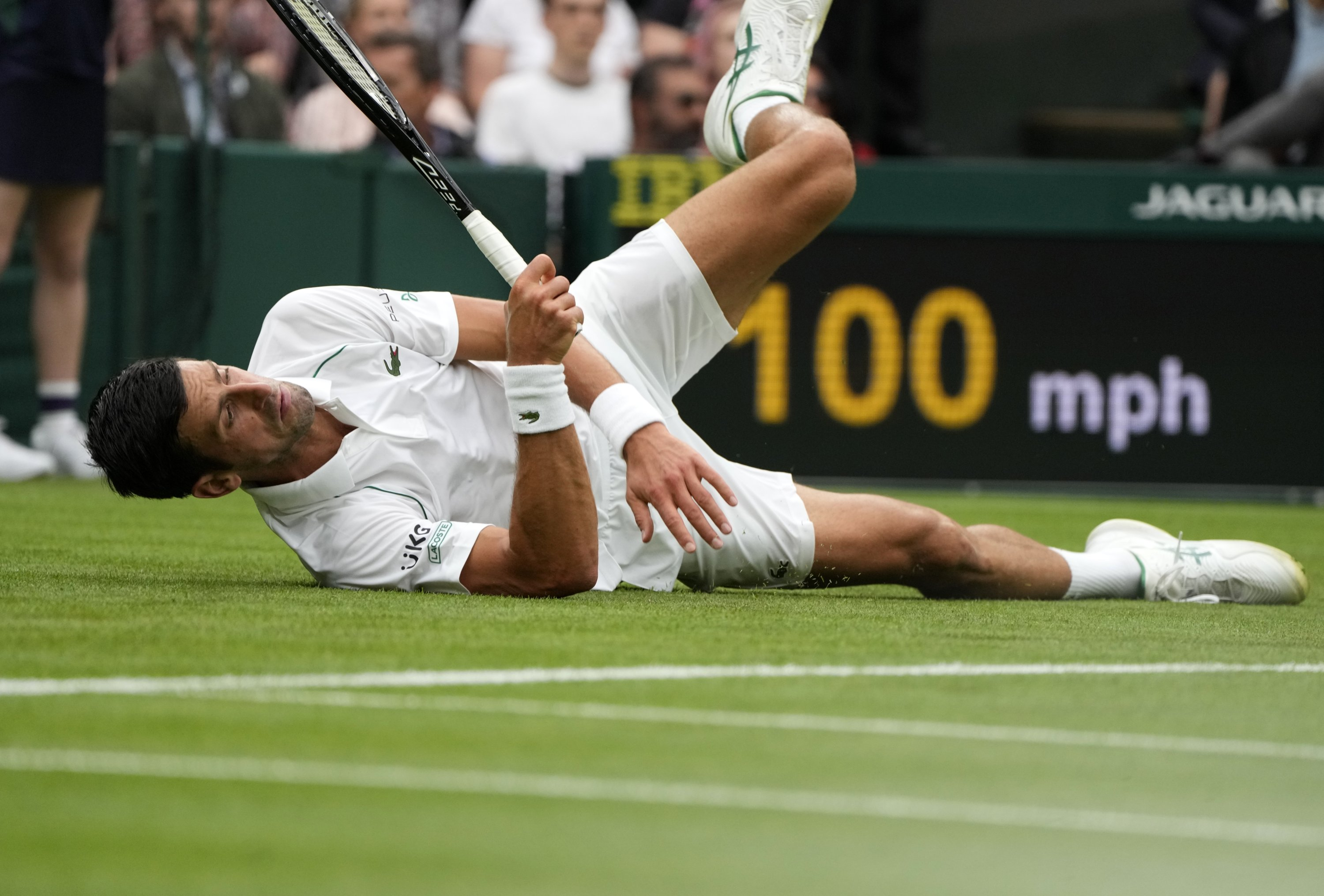 Serbia's Novak Djokovic slips on the grass during the men's singles match against Britain's Jack Draper on day one of the Wimbledon Tennis Championships in London, June 28, 2021. (AP Photo)