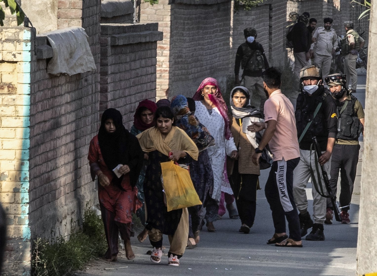 Kashmiri women and children rush for safer places near the site of a gun battle between security forces and suspected rebels on the outskirts of Srinagar, Indian-controlled Kashmir, June 28, 2021. (AP Photo)