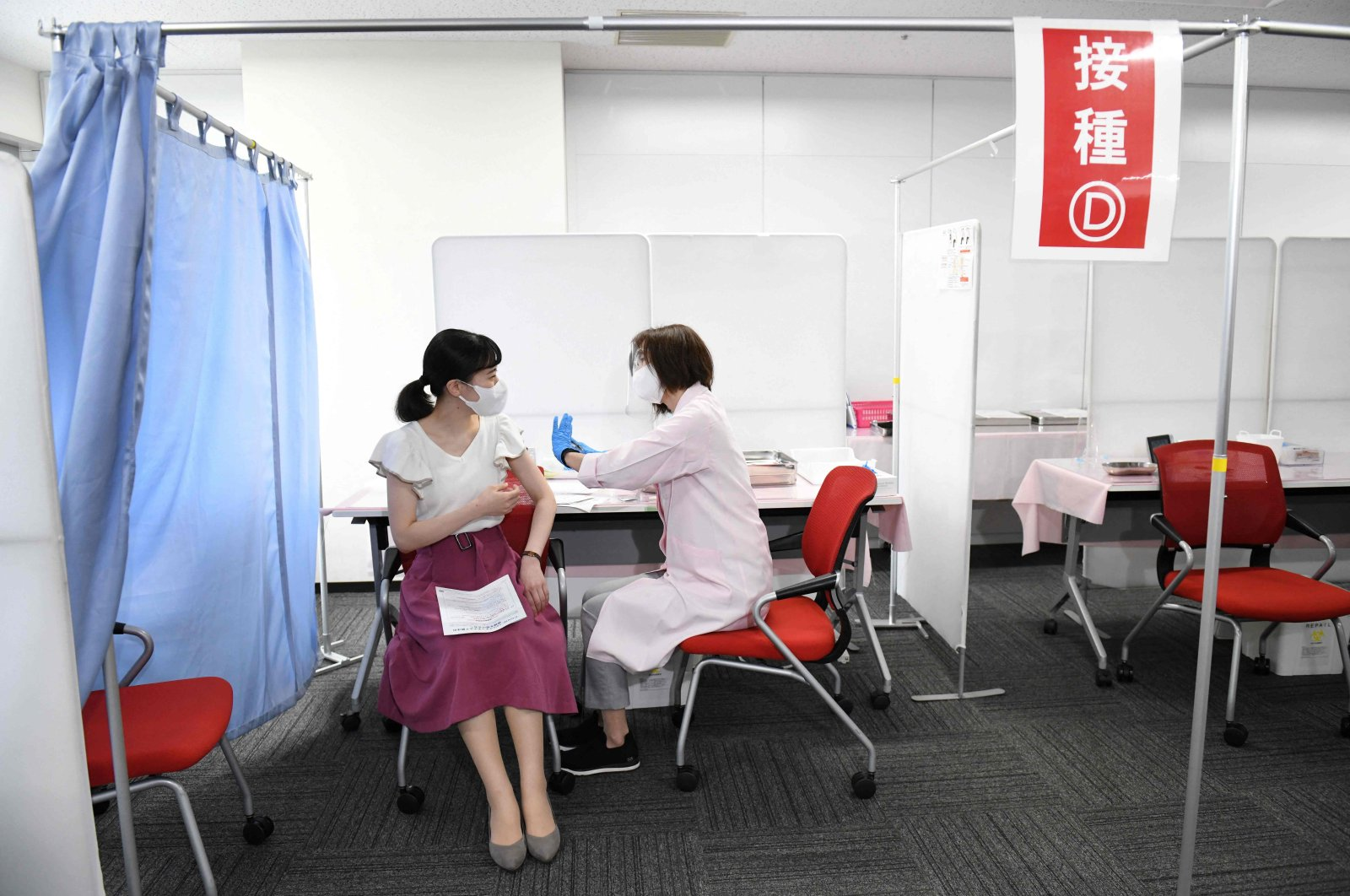 A cabin crew member (L) of Japan Airlines receives the Moderna vaccine for COVID-19 on the first day of the company's workplace vaccination campaign at Haneda Airport in Tokyo, Japan, June 14, 2021. (AFP Photo)