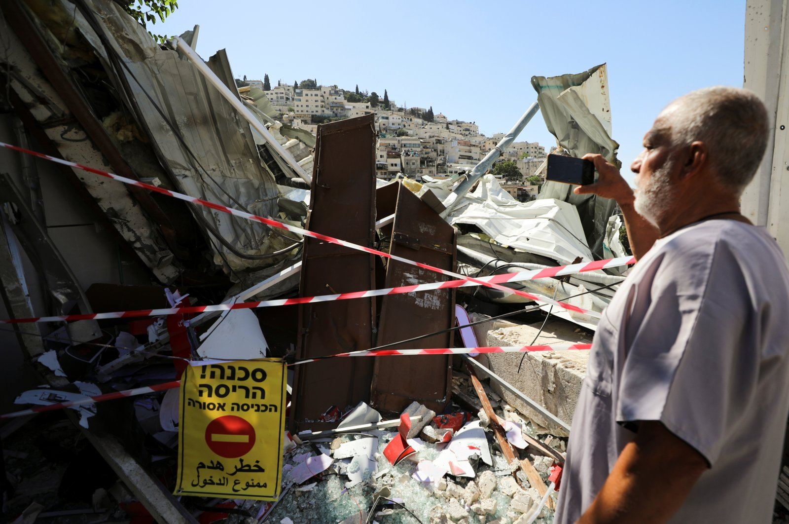 A Palestinian man uses his mobile phone as he stands near the debris of a shop that Israel demolished in the Palestinian neighborhood of Silwan in occupied East Jerusalem, Palestine, June 29, 2021. (Reuters Photo)
