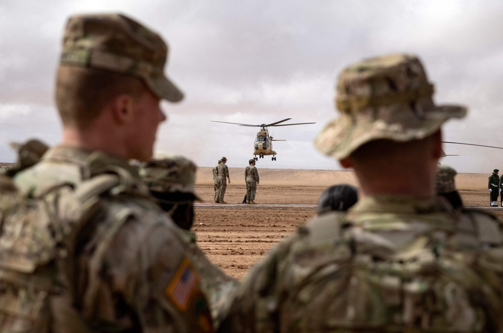 """U.S. military personnel look on as CH-47 Chinook military helicopters take off during the """"African Lion"""" military exercise in the Tan-Tan region in southwestern Morocco, June 18, 2021. (AFP Photo)"""