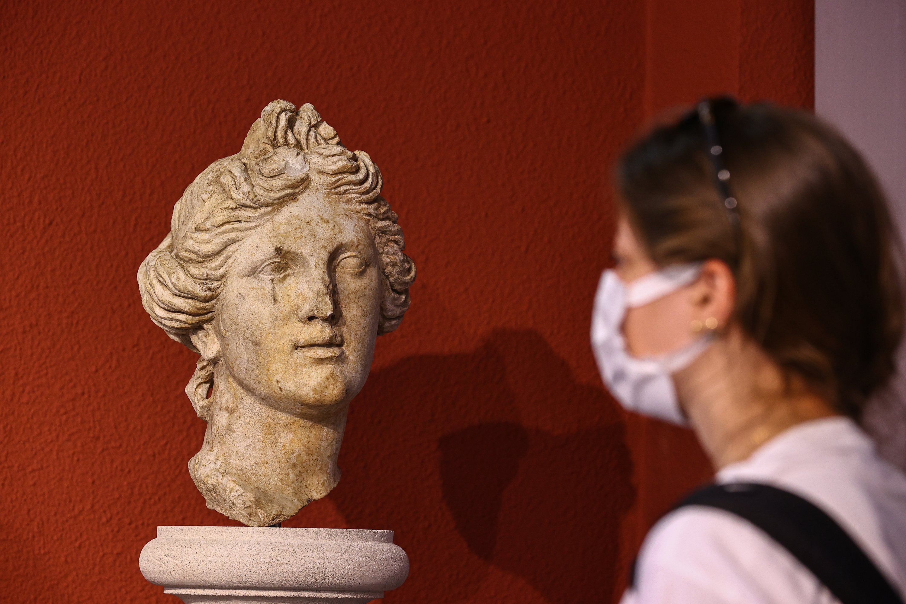 A visitor examines the head of a woman, which was the first statue found in Smyrna, at Izmir Archaeological Museum, Izmir, western Turkey, June 30, 2021. (AA Photo)