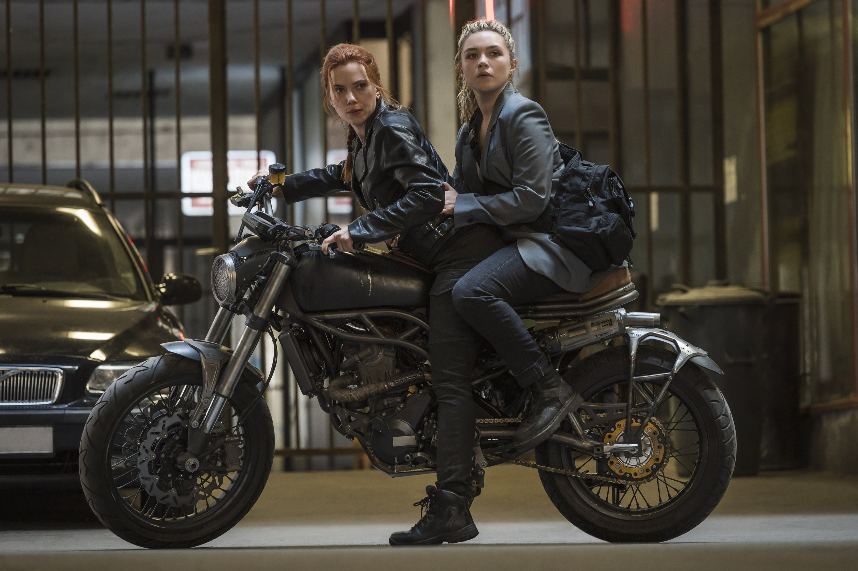 Scarlett Johansson (L) rides a motorcycle with Florence Pugh on her backin a scene from Marvel superhero film 'Black Widow.' (Disney via AP)