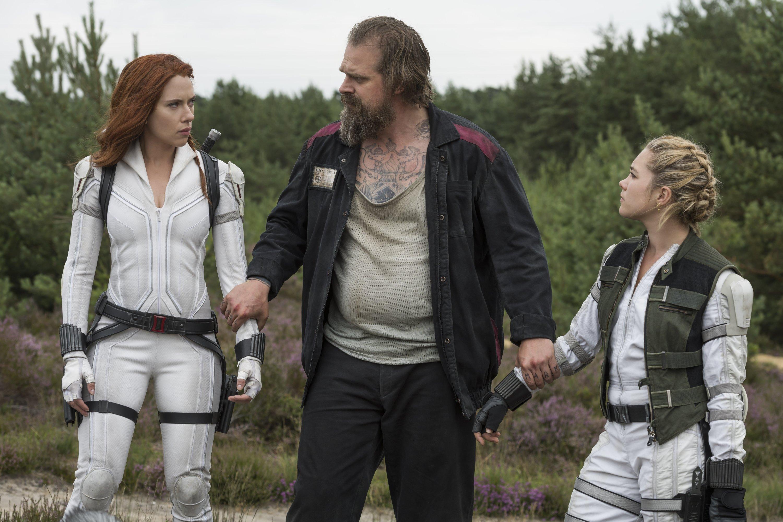 David Harbour (C) holds the hands of Scarlett Johansson (L) and Florence Pughin a scene from Marvel superhero film 'Black Widow.' (Disney via AP)