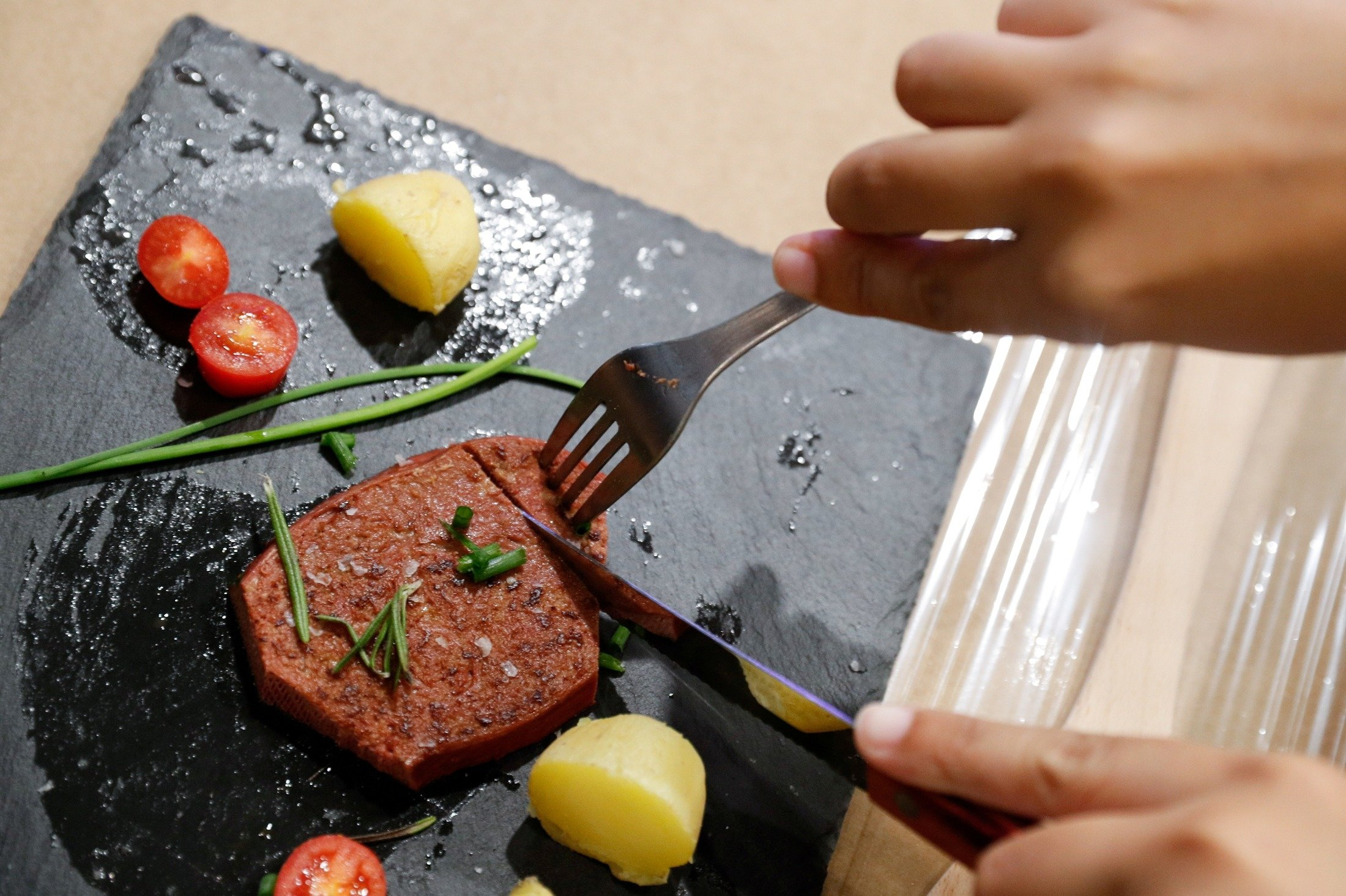 A person cuts a piece of meat printed with a 3D printer by Novameat, during the Mobile World Congress (MWC) in Barcelona, Spain, June 29, 2021. (Reuters Photo)